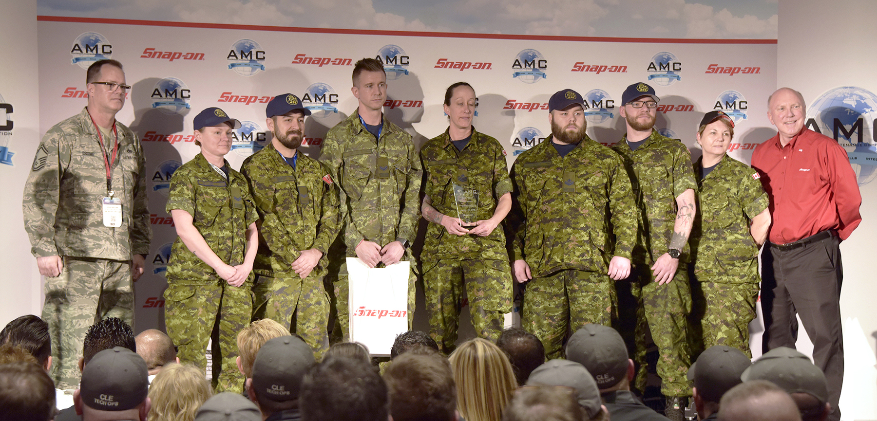 Seven people wearing Canadian disruptive pattern military uniforms, flanked by a person wearing a different disruptive pattern uniform and a person in civilian clothes, stand in a row on a stage.