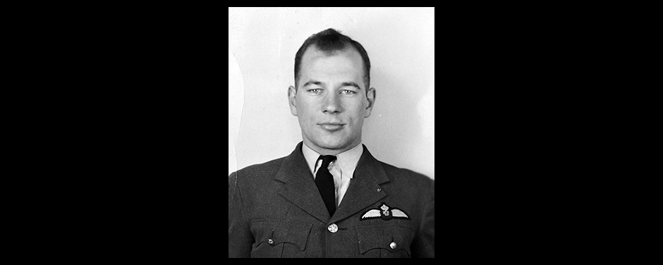 A head and shoulders photo of a bare-headed man wearing a military jacket and tie with wings sewn above the left pocket.