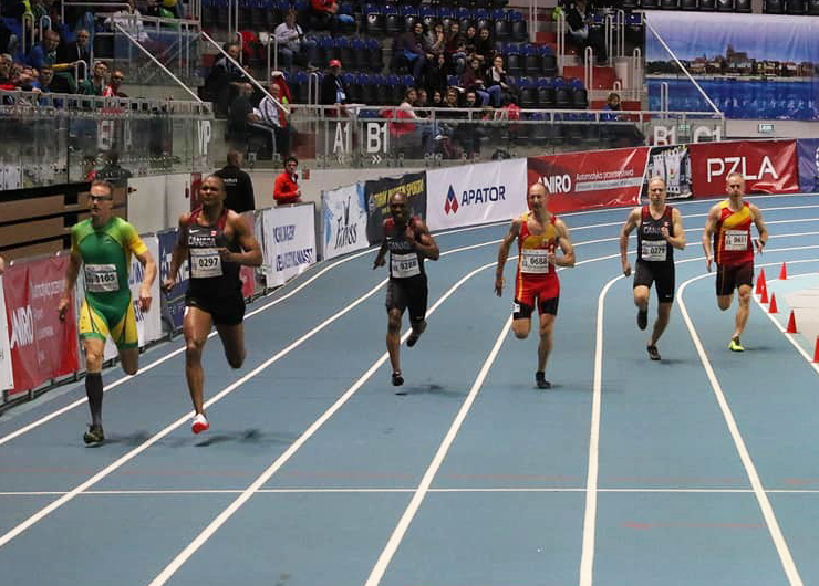 Six men run a race in lanes on an indoor track while people watch from the stands.