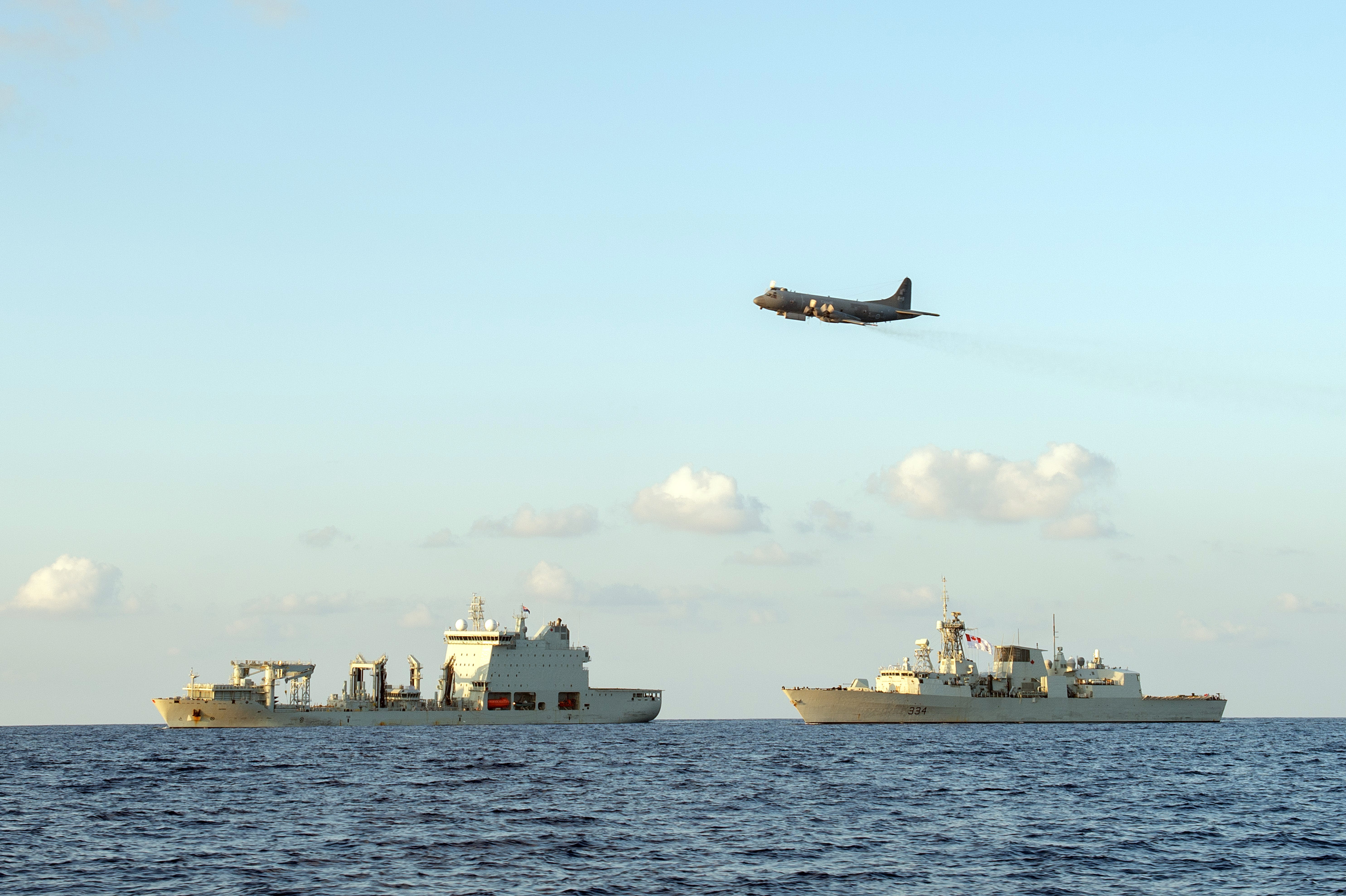 A large aircraft flies over two large ships in the open ocean.