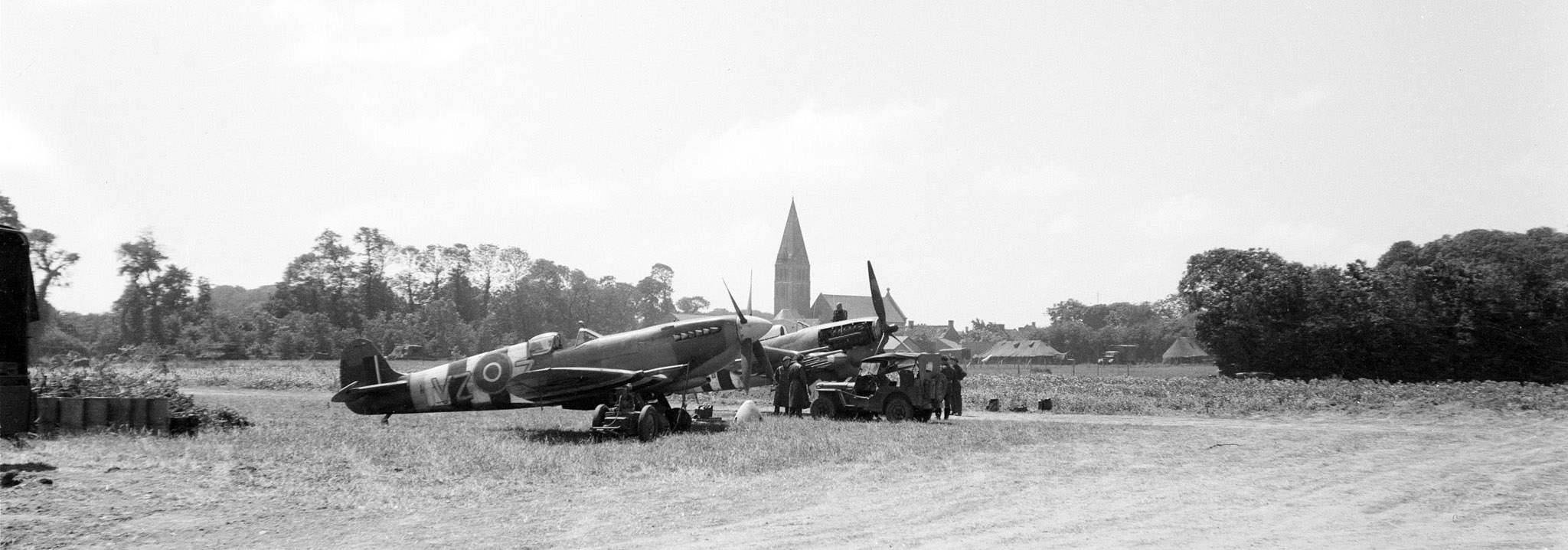 A black and white photo of propeller fighter aircraft on a field with a church spire in the background.