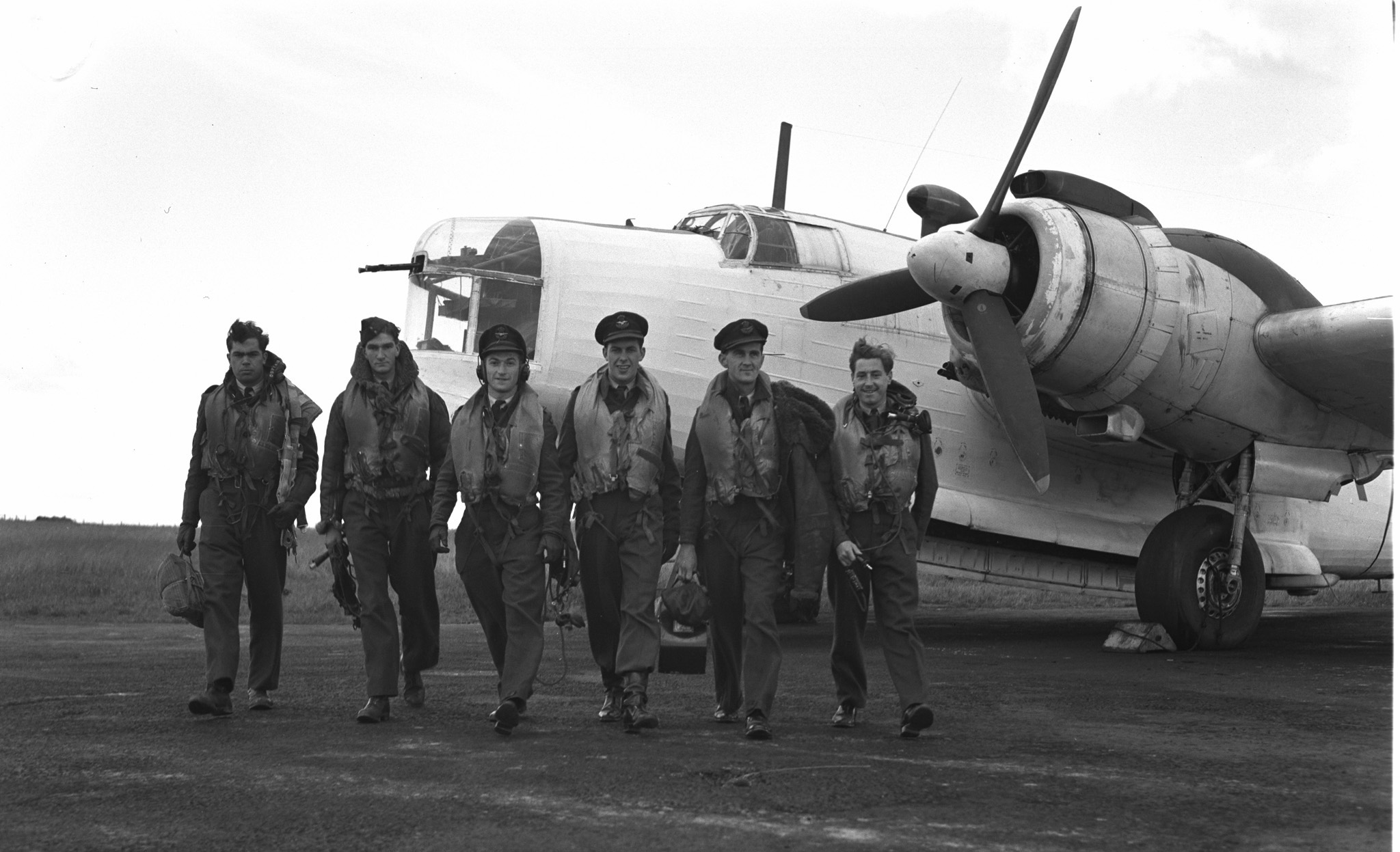 Six men wearing military uniforms and life jackets walk toward the camera, away from a large twin-propeller aircraft.