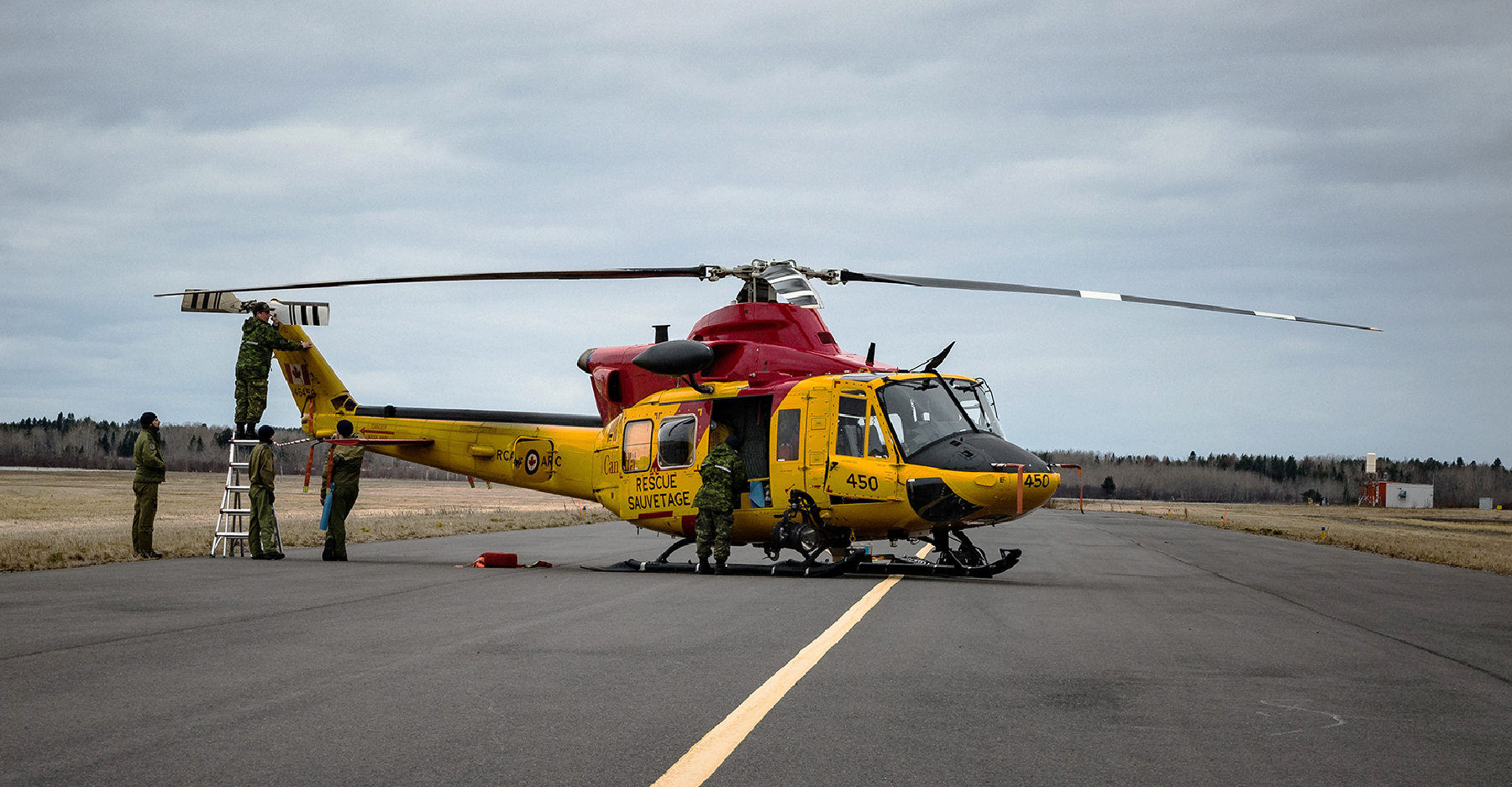 A helicopter painted in yellow and red search and rescue colours rests on the tarmac with people wearing military uniforms working on or near it.