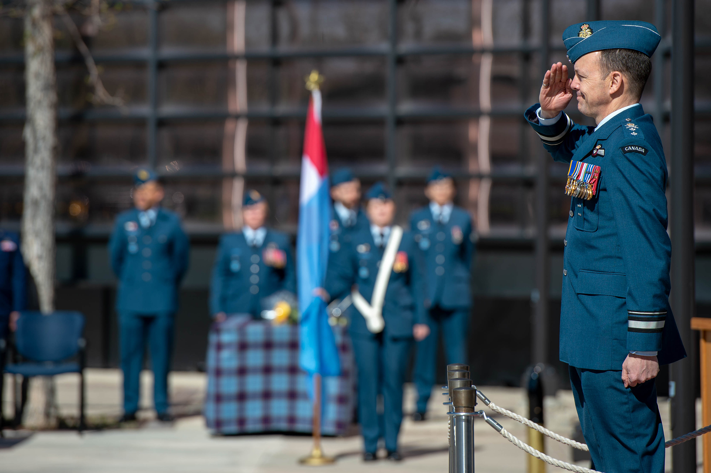 A man wearing a military uniform stands on a platform and salutes.