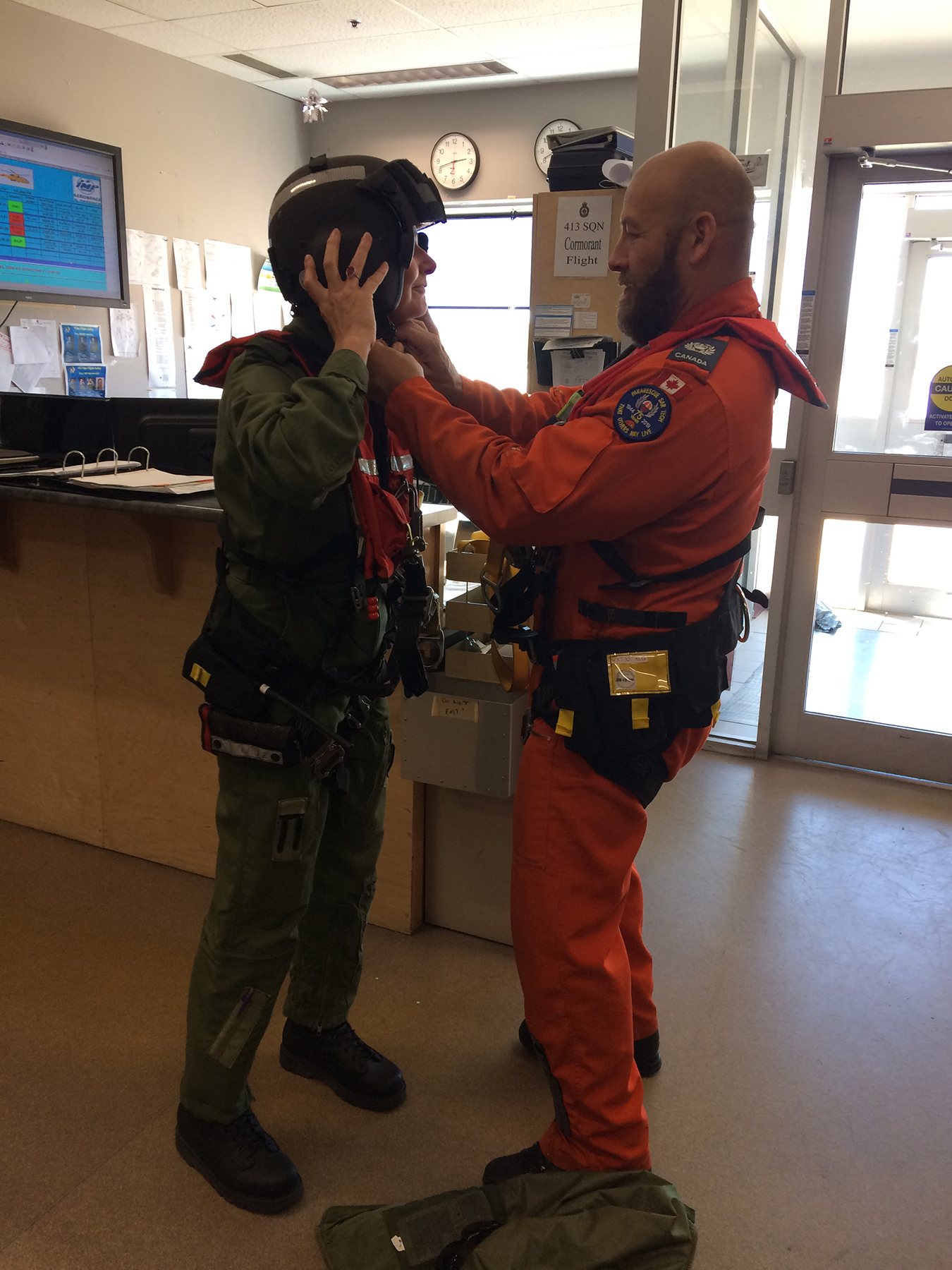 Search and rescue technician Master Warrant Officer Chris Lamothe fits 415 (Long Range Patrol Force Development) Squadron Honorary Colonel Sandra Snow in a harness and helmet for her June 12, 2019, flight in a 413 (Transport and Rescue) Squadron CH-149 Cormorant helicopter. PHOTO: Sara White