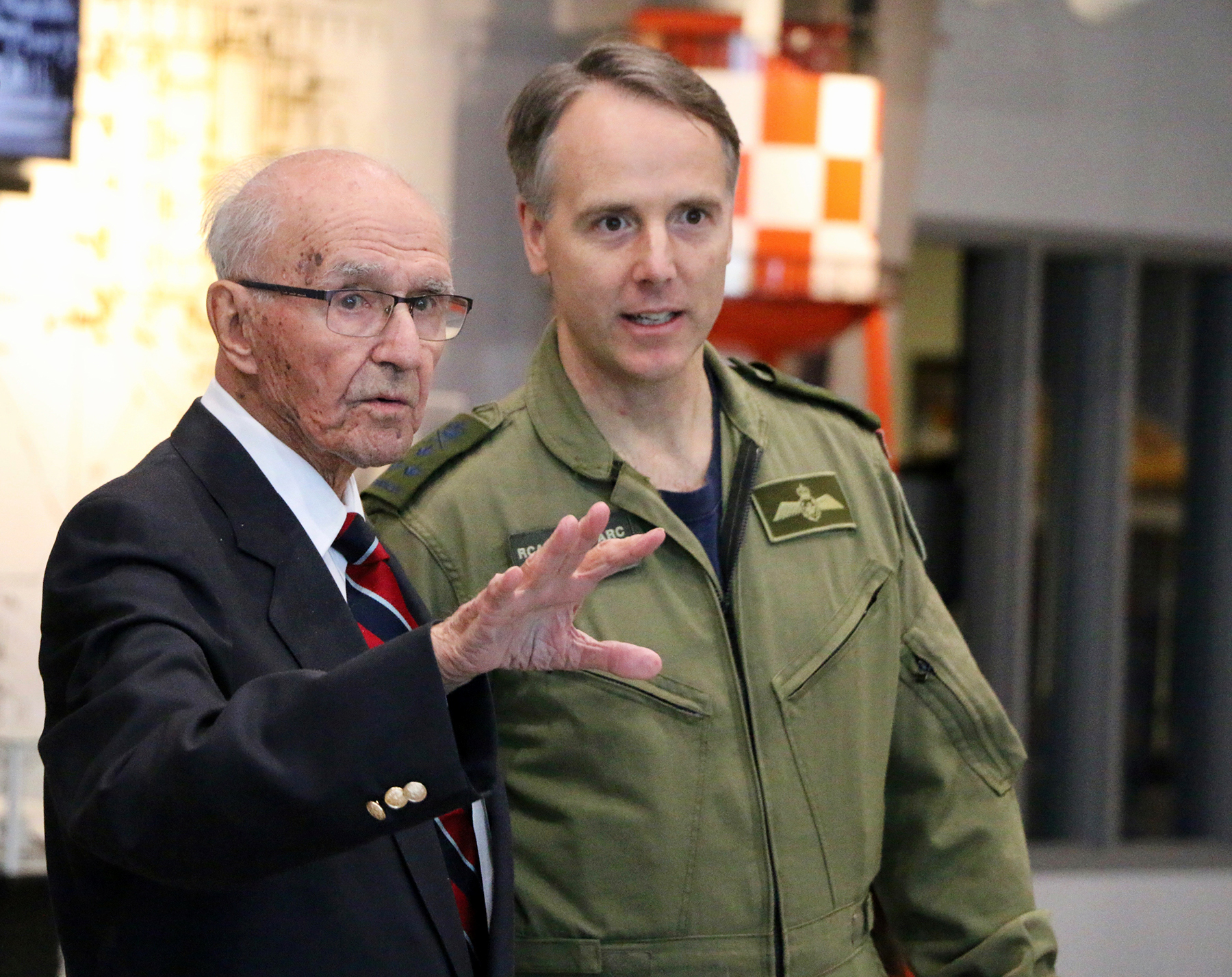 A photograph of an older man wearing a dark blazer, white shirt and striped tie standing next to a younger man wearing an olive green flight suit.