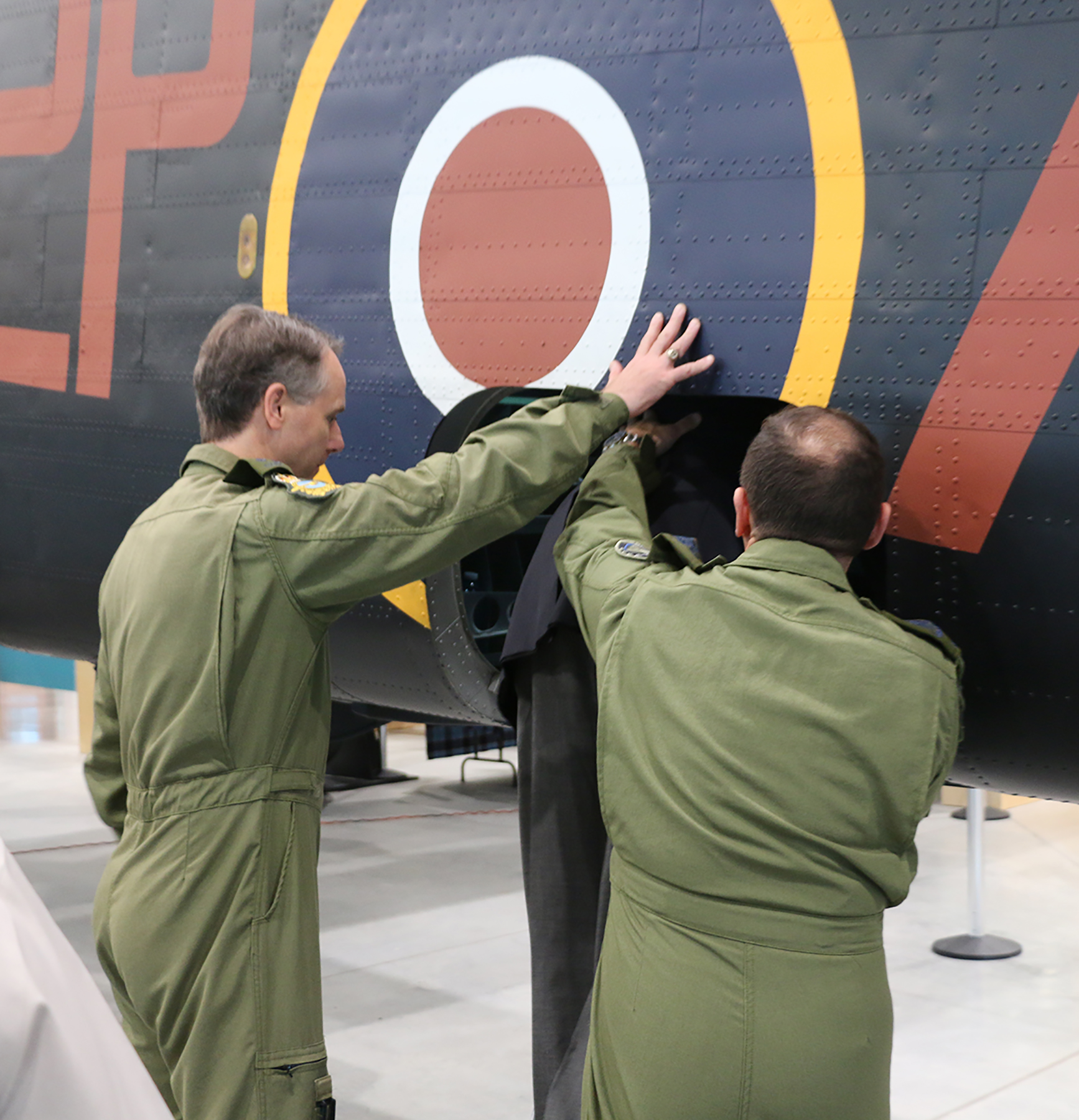 At the National Air Force Museum of Canada in Trenton, Ontario, commander of the Royal Canadian Air Force Lieutenant-General Al Meinzinger (left) lends a hand on May 15, 2019, as Flight Lieutenant (retired) Stuart Vallières climbs into a Handley Page Halifax bomber for the first time since he was shot down in one over occupied Europe in 1944, and taken prisoner. PHOTO: Makala Chapman