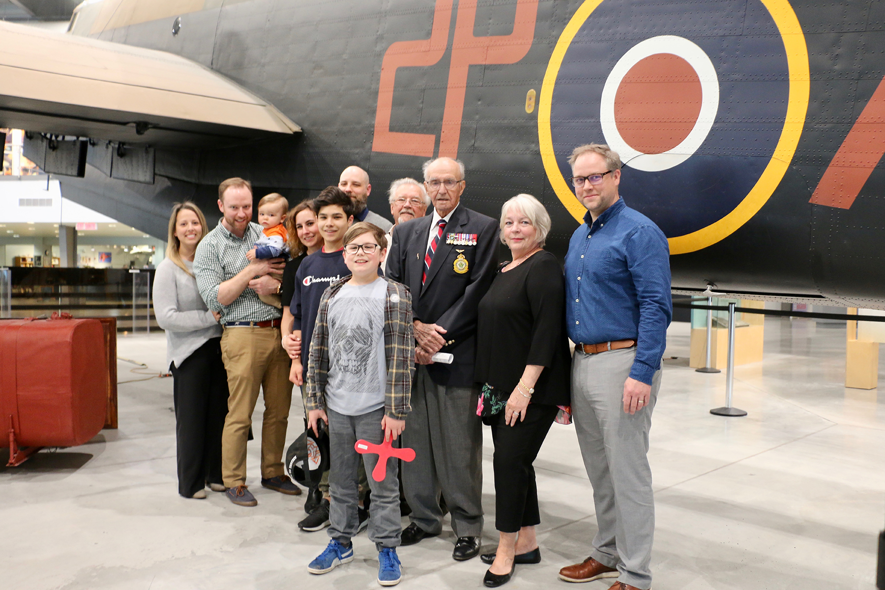 Flight Lieutenant (retired) Stuart Vallières (third right) stands with members of his family beside the Halifax bomber at the National Air Force Museum of Canada in Trenton, Ontario, on May 15, 2019. PHOTO: Makala Chapman