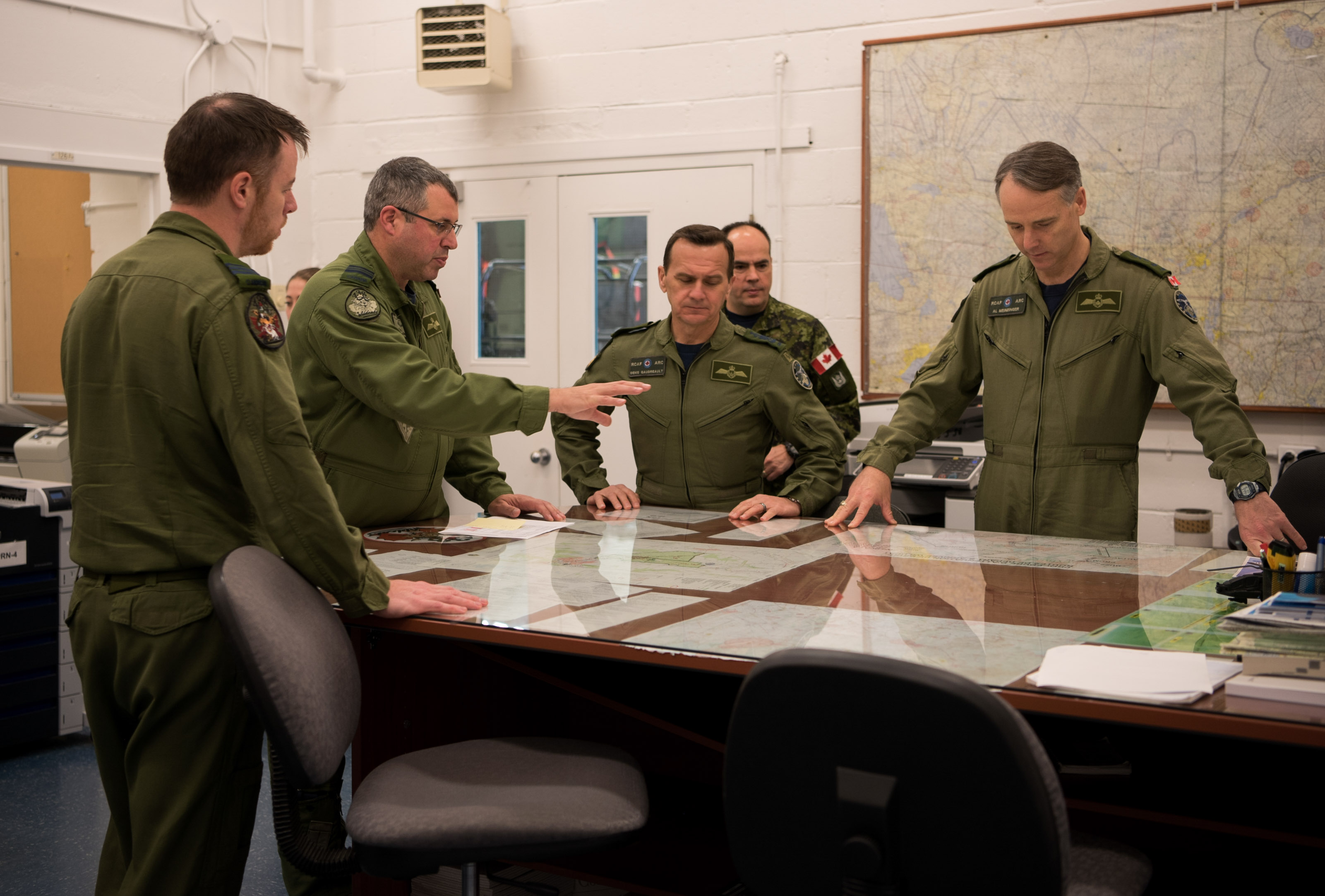Five men in military uniforms talk while standing around a table covered with a sheet of glass, under which are documents.