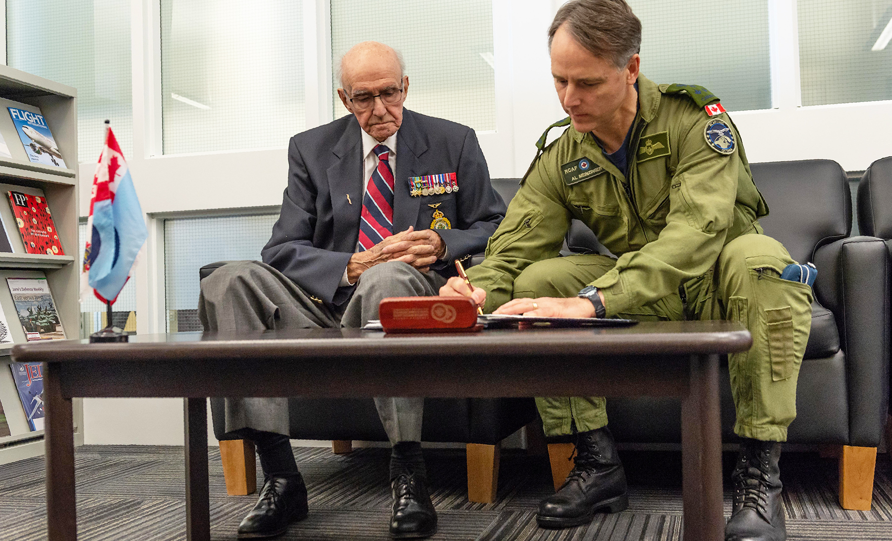 Commander of the Royal Canadian Air Force Lieutenant-General Al Meinzinger and Flight Lieutenant Vallières sign the Royal Canadian Air Force Aerospace Warfare Centre guestbook at 8 Wing, Trenton, Ontario, on May 15, 2019. PHOTO: Corporal Ken Beliwicz, TN12-2019-0119-001-003