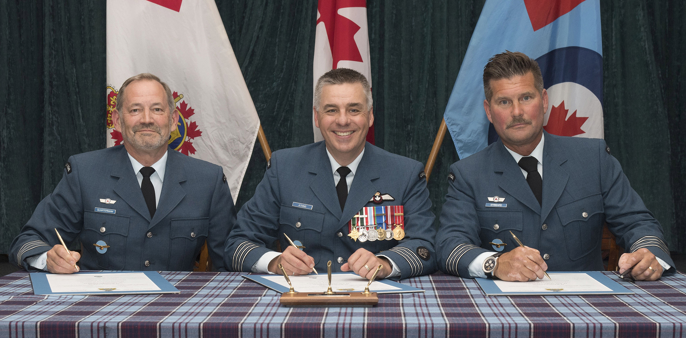 Three men, wearing military uniforms and holding pens, sit behind a tartan covered table. In front of each is a large document.