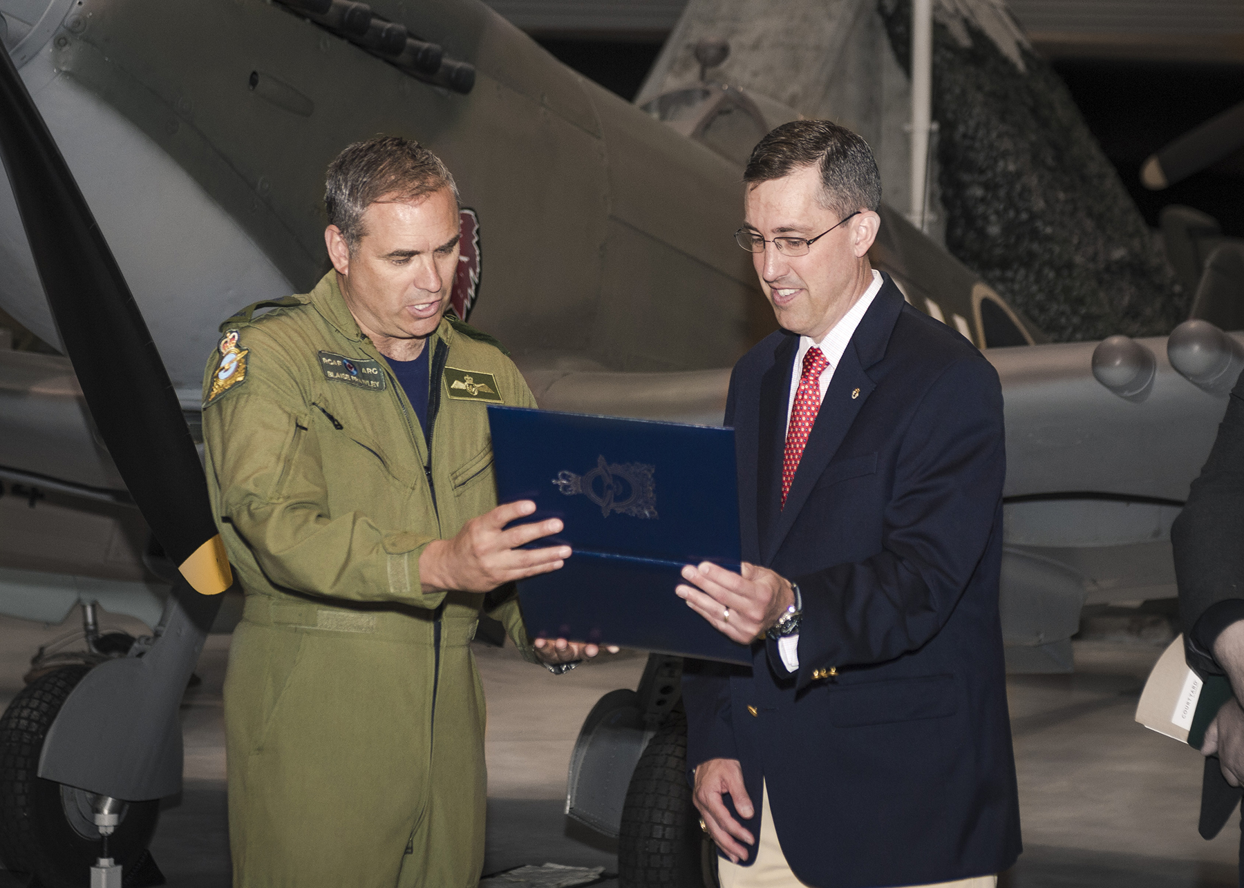 A man wearing an olive green flight suit over a navy blue T-shirt and a man wearing a dark blue blazer, cream pants and a shirt and tie, look at the contents of a dark blue leather-covered folder with an image of a gold crest on the front. They are indoors; behind them is an aircraft.