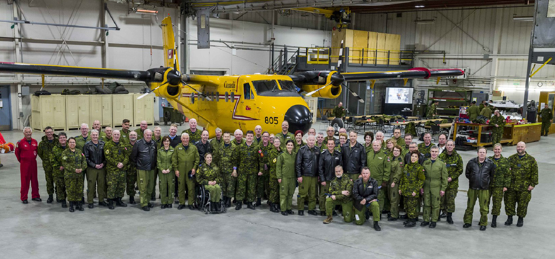 A large group of people, one wearing an orange flightsuit and the rest in olive green, with some in black leather jackets, gather beside a small yellow twin-engine ai\rcraft.