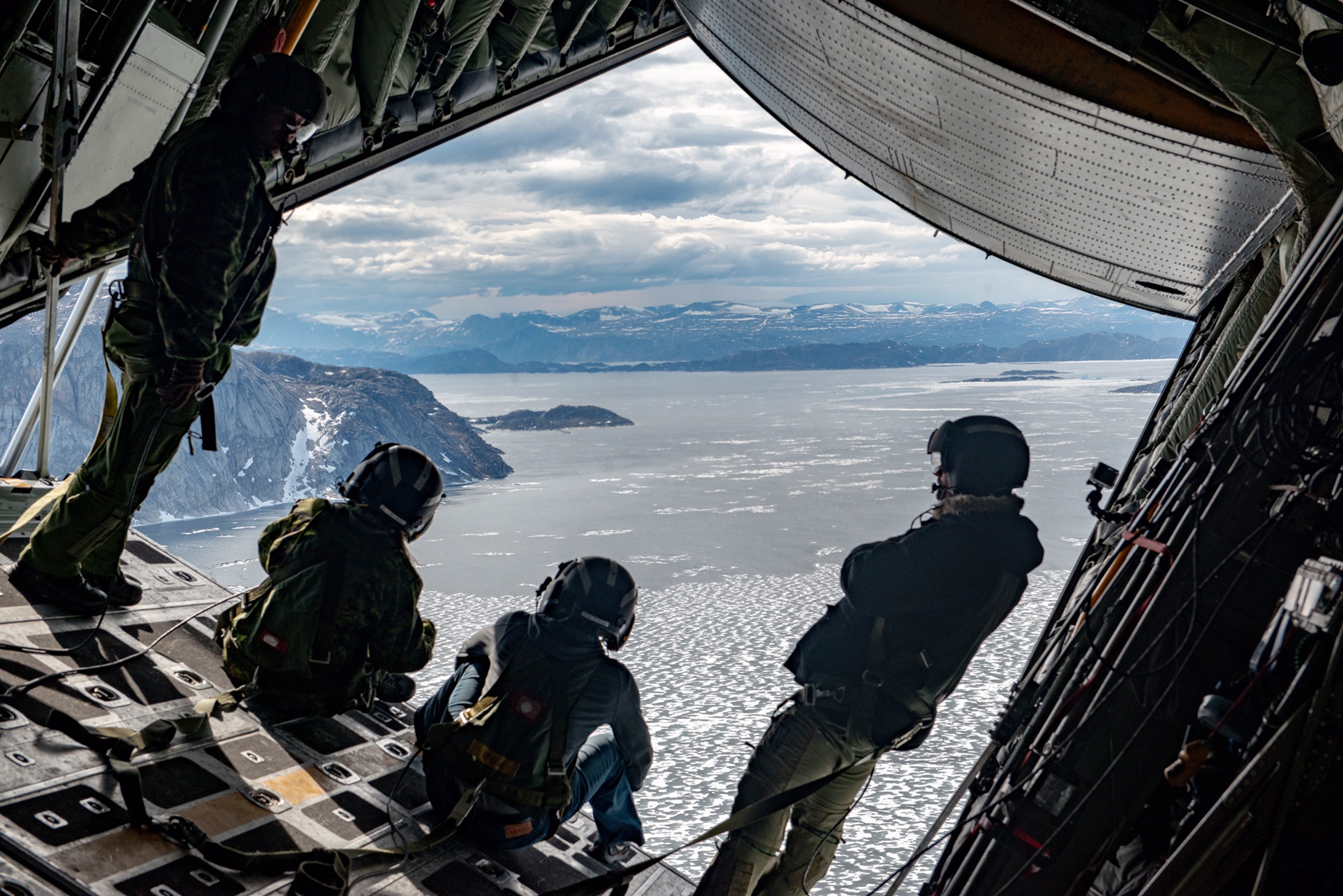 From left, Corporal Joe Gervais, Corporal J.F. Paradis, Lieutenant Junior Grade Bryan Brasher, and Master Corporal Marc Lapensee, check out the stellar view of Baffin Island from the ramp of a CC-130 Hercules aircraft during the annual Arctic Buoy drop mission. PHOTO: Ignatius Rigor