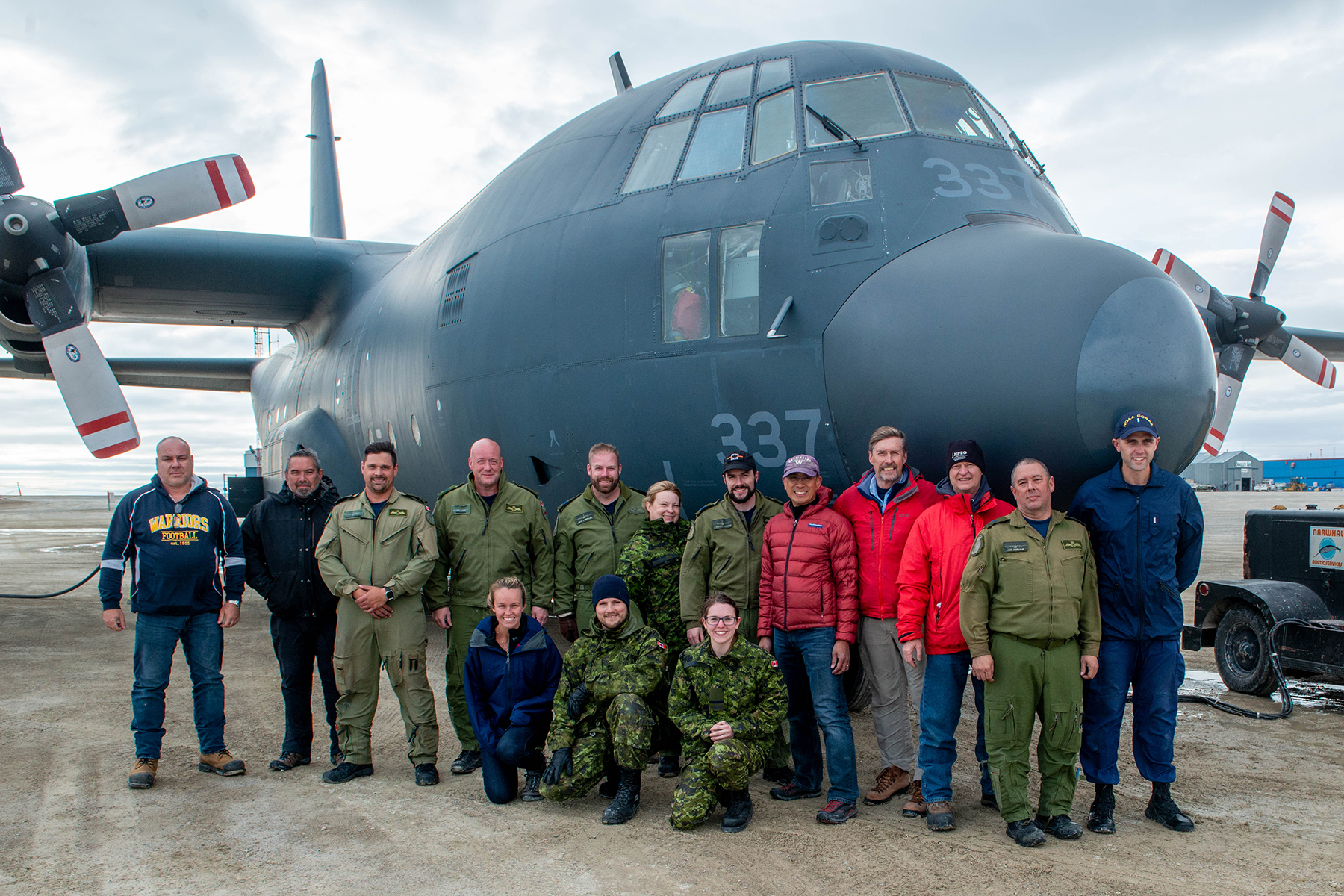 2019 Arctic Buoy drop mission team members, comprising RCAF aircrew and seven civilians gather for a photo with their ride, a CC-130 Hercules aircraft. Front row, from left: US Navy Midshipman Annie Shea; Technician Corporal J.F. Paradis; and Second Lieutenant Danielle Beland. Back row, from left: Shawn Morissette (Defence Research Development Canada/DND; Rich DeVall (Environment and Climate Change Canada); Loadmaster Master Corporal Marc Lapensee; Flight Engineer Warrant Officer Mike Mar; First Officer Captain Jeff LaBrash; Navigator Captain Sarah Fralick; Captain Tristan Dobson; Ignatius Rigor (University of Washington); Vaughn Cosman (Defence Research Development Canada/DND); Jim Johnson (University of Washington); Loadmaster Corporal Joe Gervais; and Lieutenant Junior Grade Bryan Brasher (US National Oceanic and Atmospheric Administration). PHOTO: Ignatius Rigor
