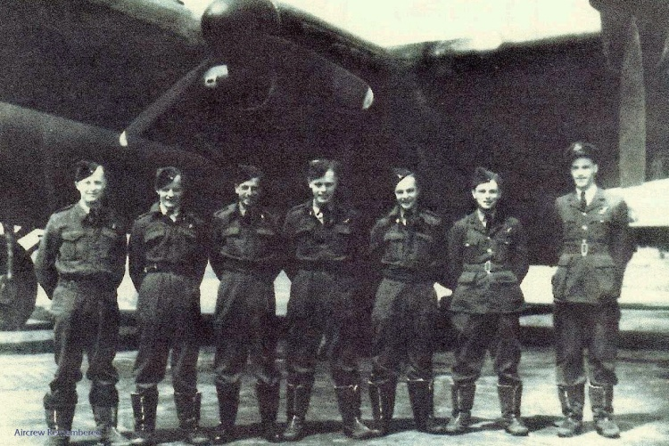 Seven men in military uniforms stand in a row with their hands behind their backs in front a large propeller-driven aircraft.
