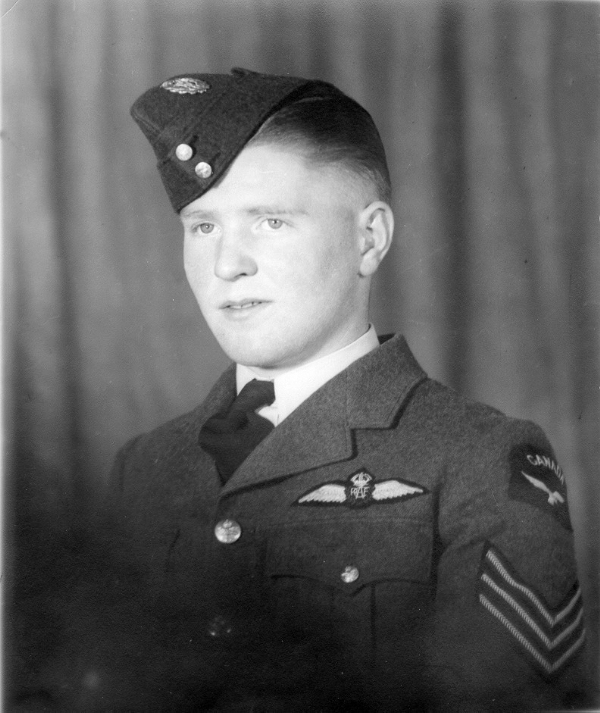 "Vintage photo of a young man wearing a military uniform, including ""wedge"" cap, tunic and tie."