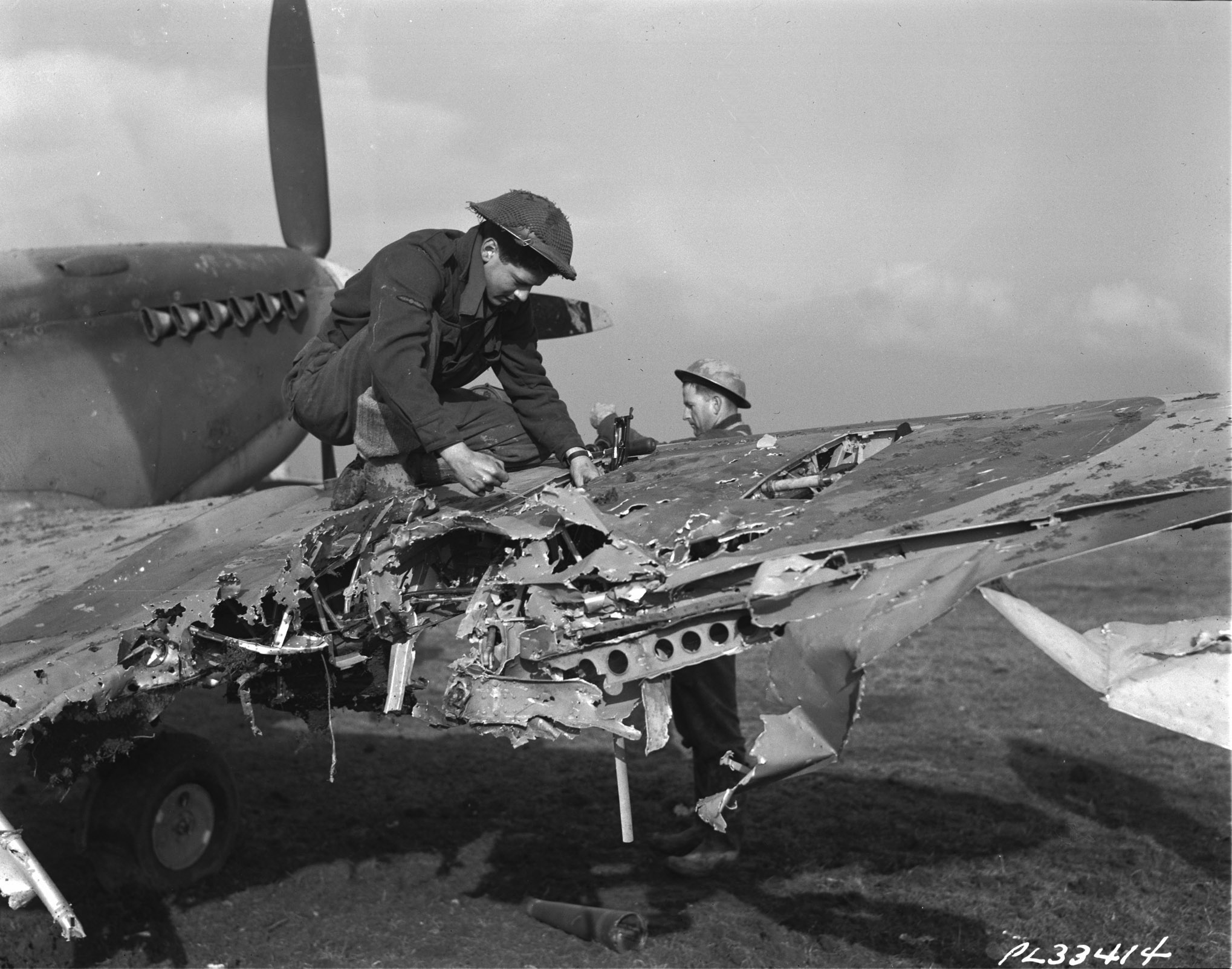 A man kneels on the damaged wing of a small aircraft