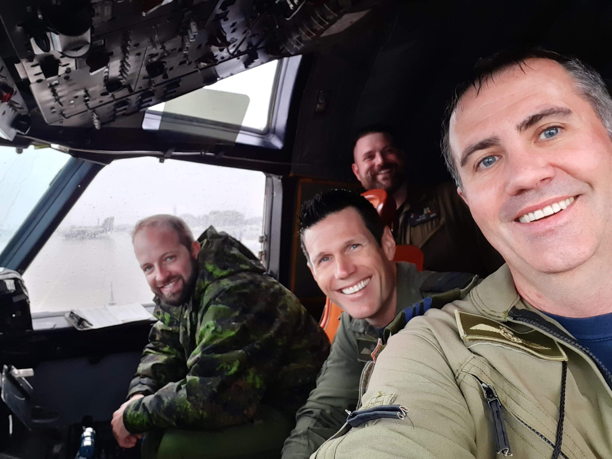 Four military persons inside an aircraft cockpit.