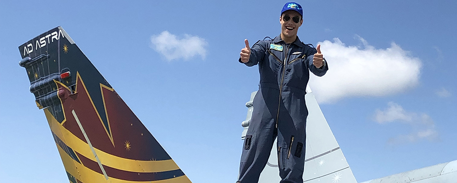 Under a blue sky, a young man wearing a dark blue flight suit and cap stands on the wing of a fighter aircraft with a decoratively painted tail and gives a thumbs-up.