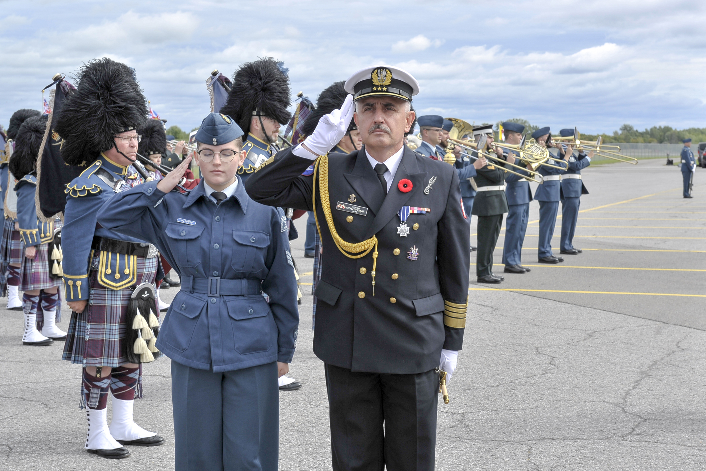 A youth wearing an Air Force-style uniform and a man wearing a naval uniform face the camera and salute. In the background are a brass band and bagpipers.