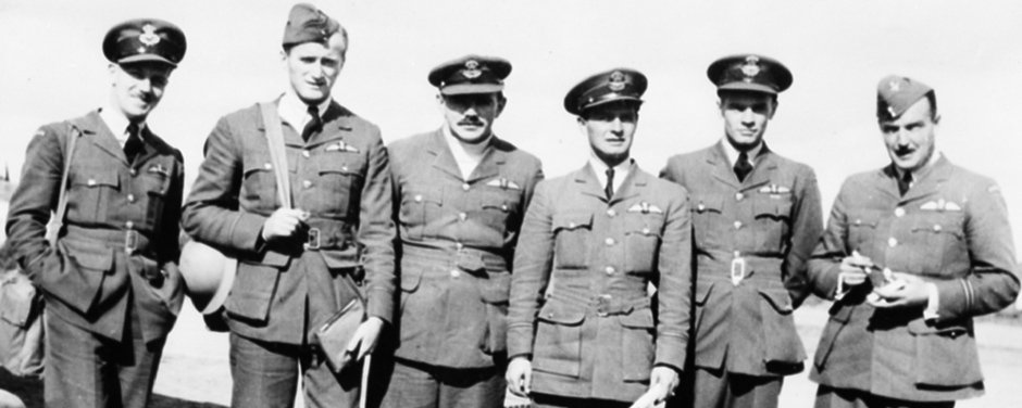 slide - Six men wearing military uniforms with belted tunics, stand in a row.