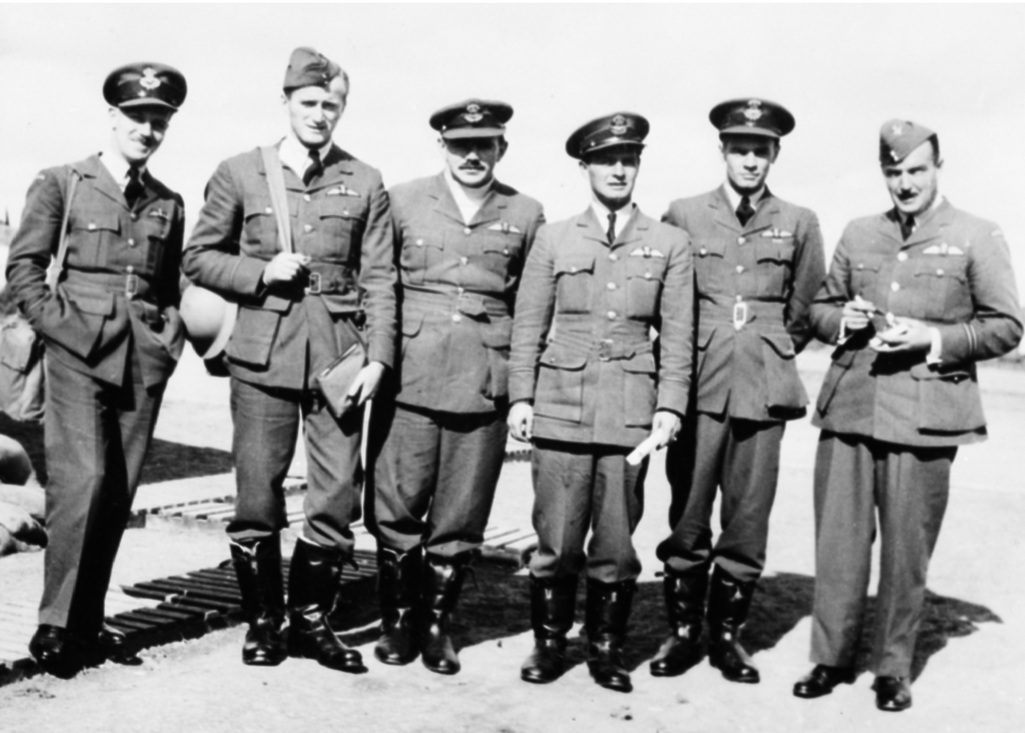 Six men wearing military uniforms with belted tunics, stand in a row.