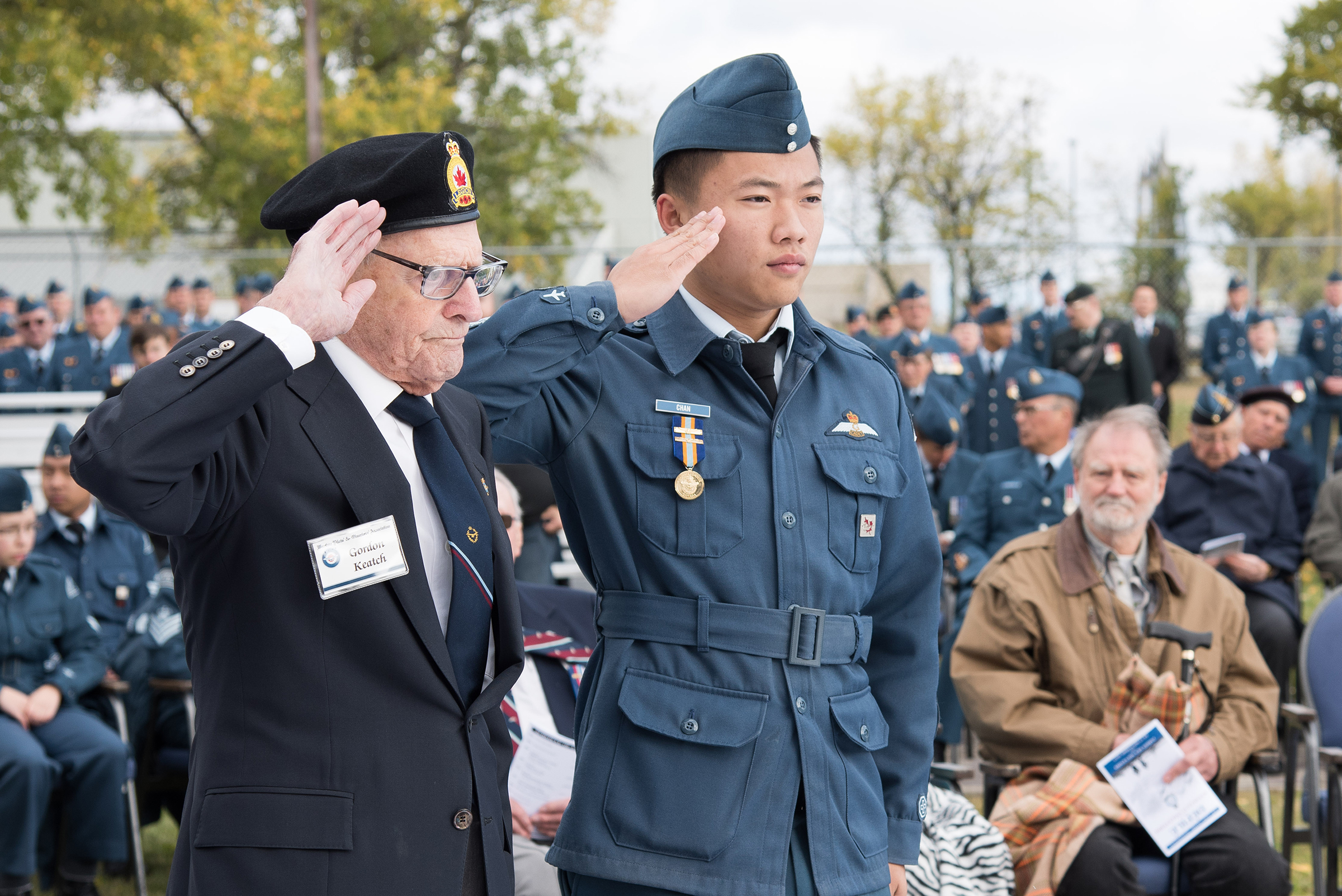 An elderly man wearing a jacket, tie and beret and a young man wearing a military uniform stand side by side and salute.
