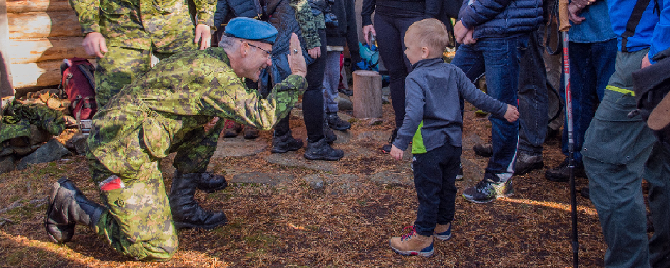 slide - A man wearing a disruptive-pattern uniform and a blue beret prepares to be high-fived by a toddler, while a second man in a similar uniform and a large crowd of people watch.
