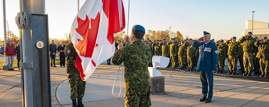 slide - In the foreground, a person wearing a camouflage pattern uniform raises a Canadian flag, while a man wearing an RCAF dress uniform salutes and additional personnel in the background salute.