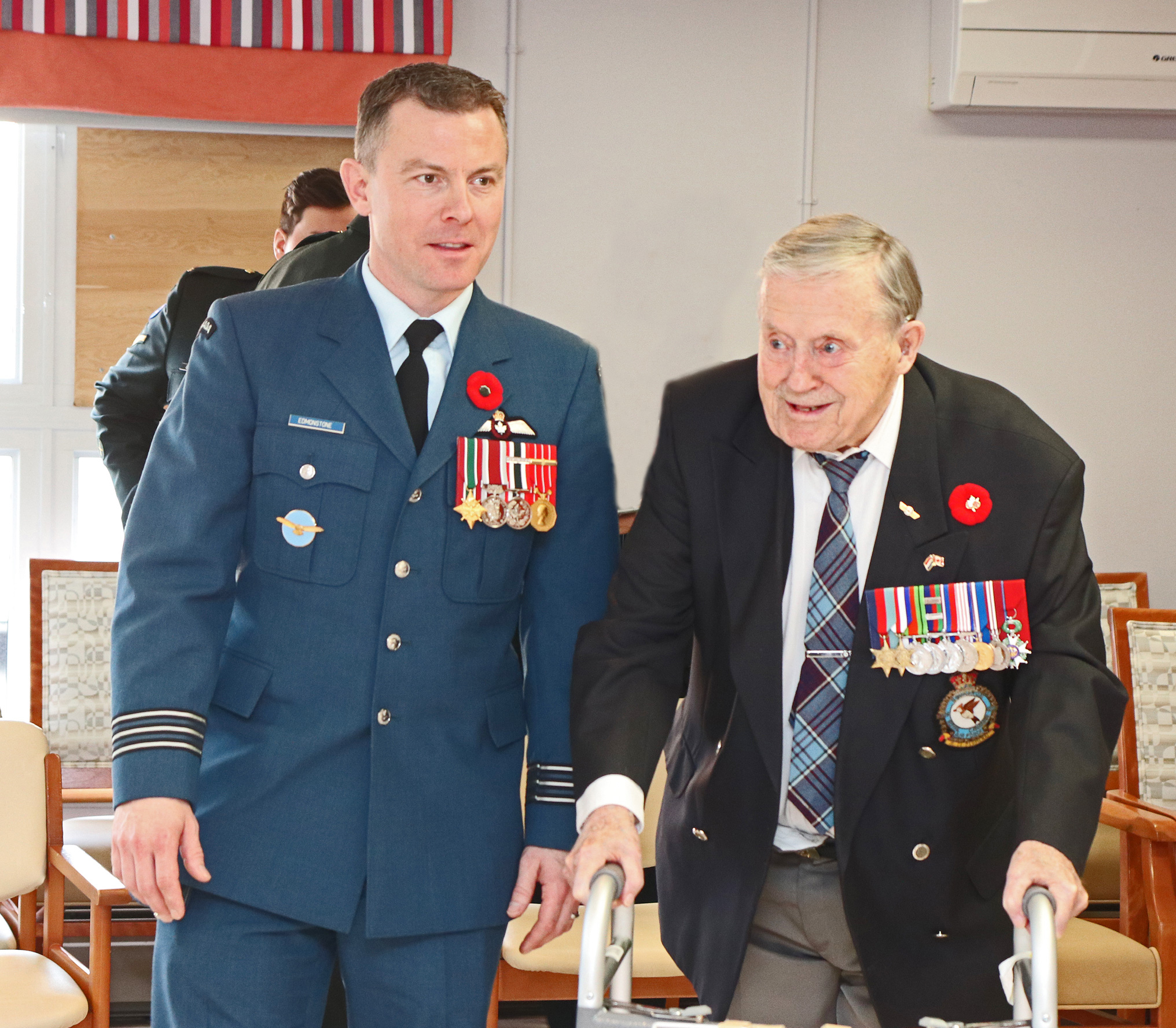 A man wearing an air force uniform stands beside an older man leaning on a metal walker and wearing a blazer and air force tartan tie. Both have several medals on their jackets.
