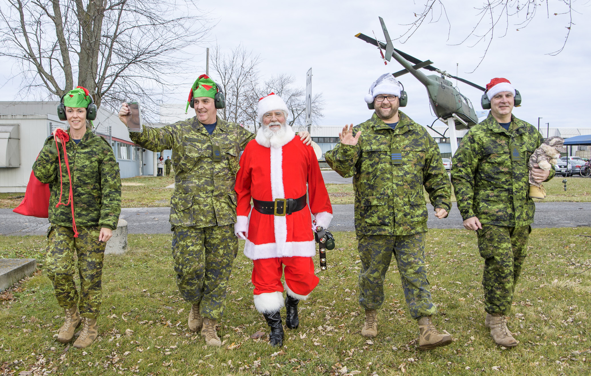 Four people, wearing disruptive pattern combat uniforms and Santa or elf-style hats, walk across a grassy area with a person dressed as Santa.