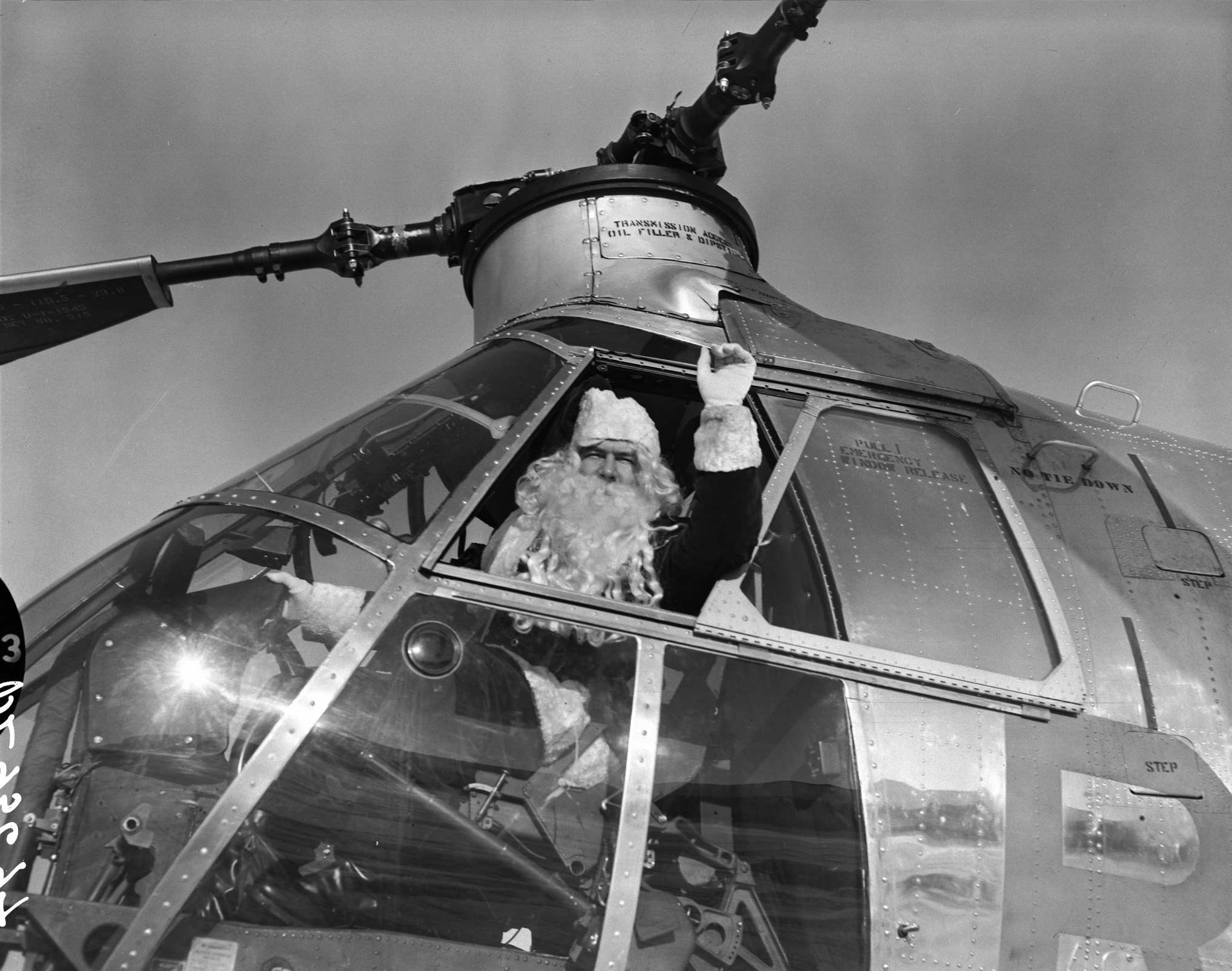 A vintage photo of Santa Claus seated in the cockpit of a helicopter, waving through the open side window.