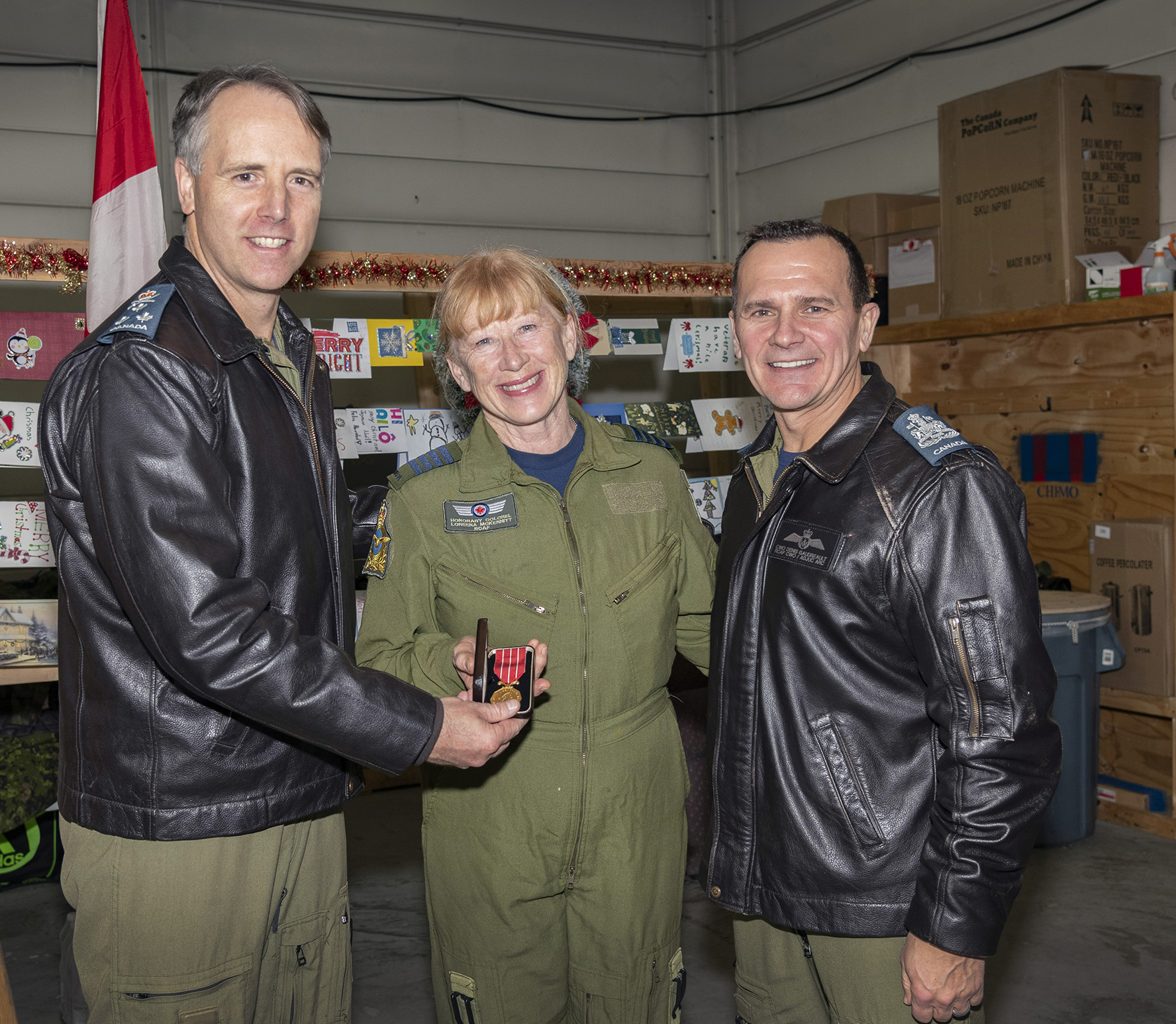 Three people, all wearing military flight suits, stand in a row as one hands a small box with a medal in it to another.