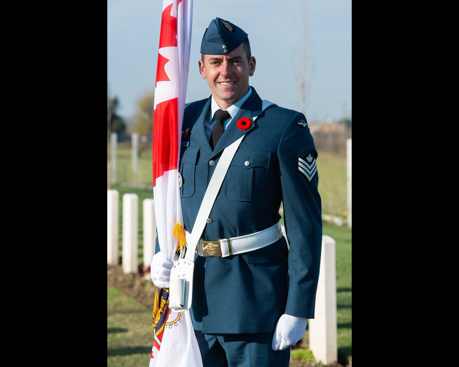 A man wearing an RCAF uniform holds a flag as he stands in a cemetery.