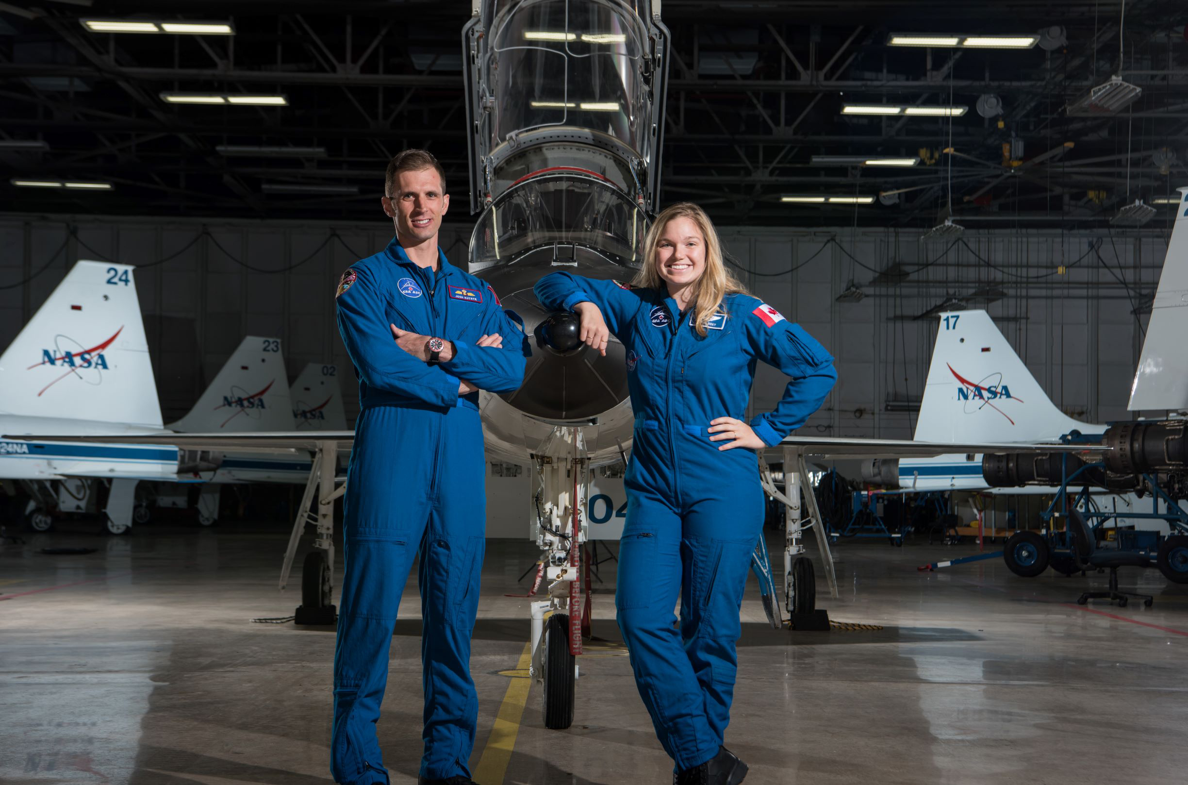 A man and a woman wearing flight suits stand in front of a fighter aircraft in a hangar.