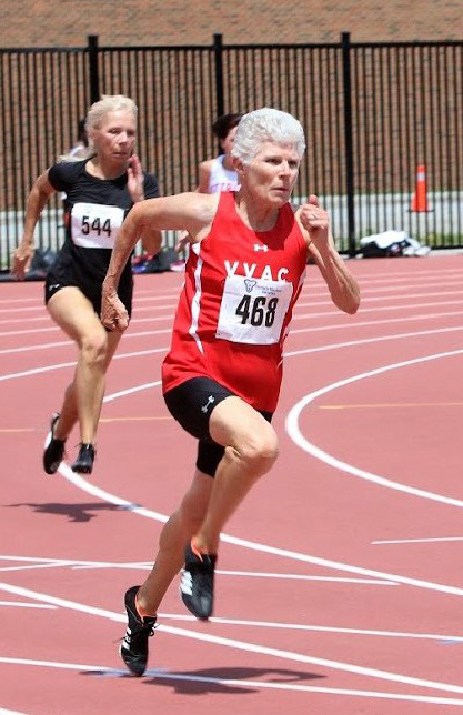 A grey-haired woman leads women in a race on an outdoor track.