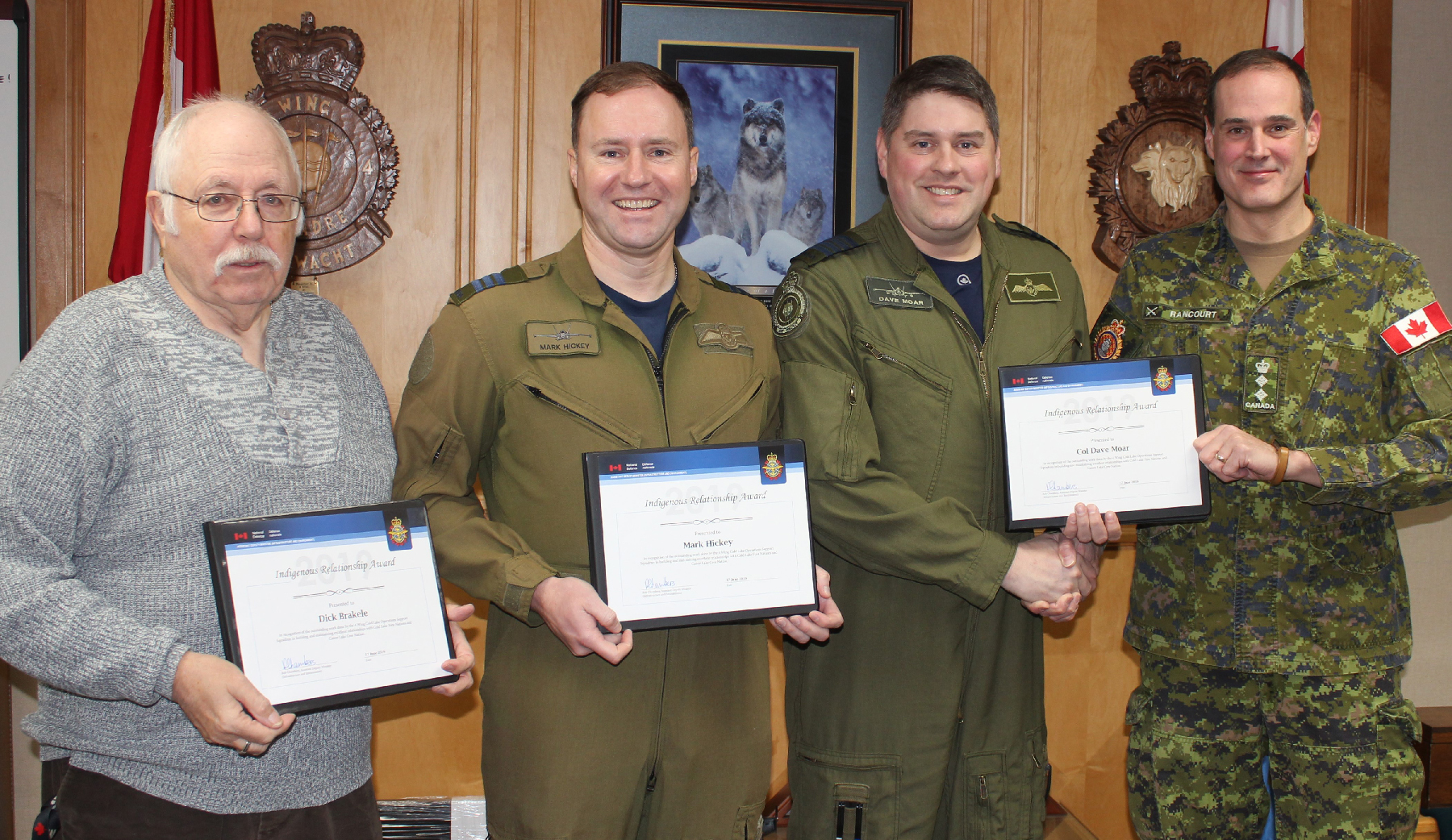 Four men, three in uniform and one in civilian dress, stand in a row holding certificates.