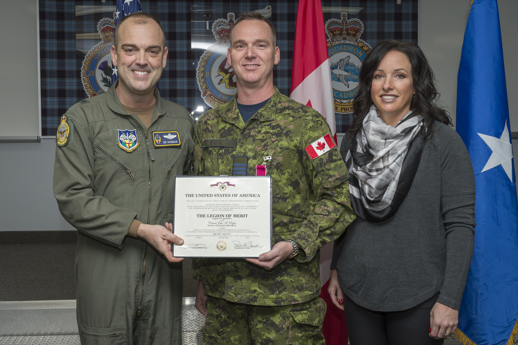 A photo of two men holding a certificate, one wearing a green flight suit and the other a military camouflage uniform, and a woman dressed in civilian clothes.