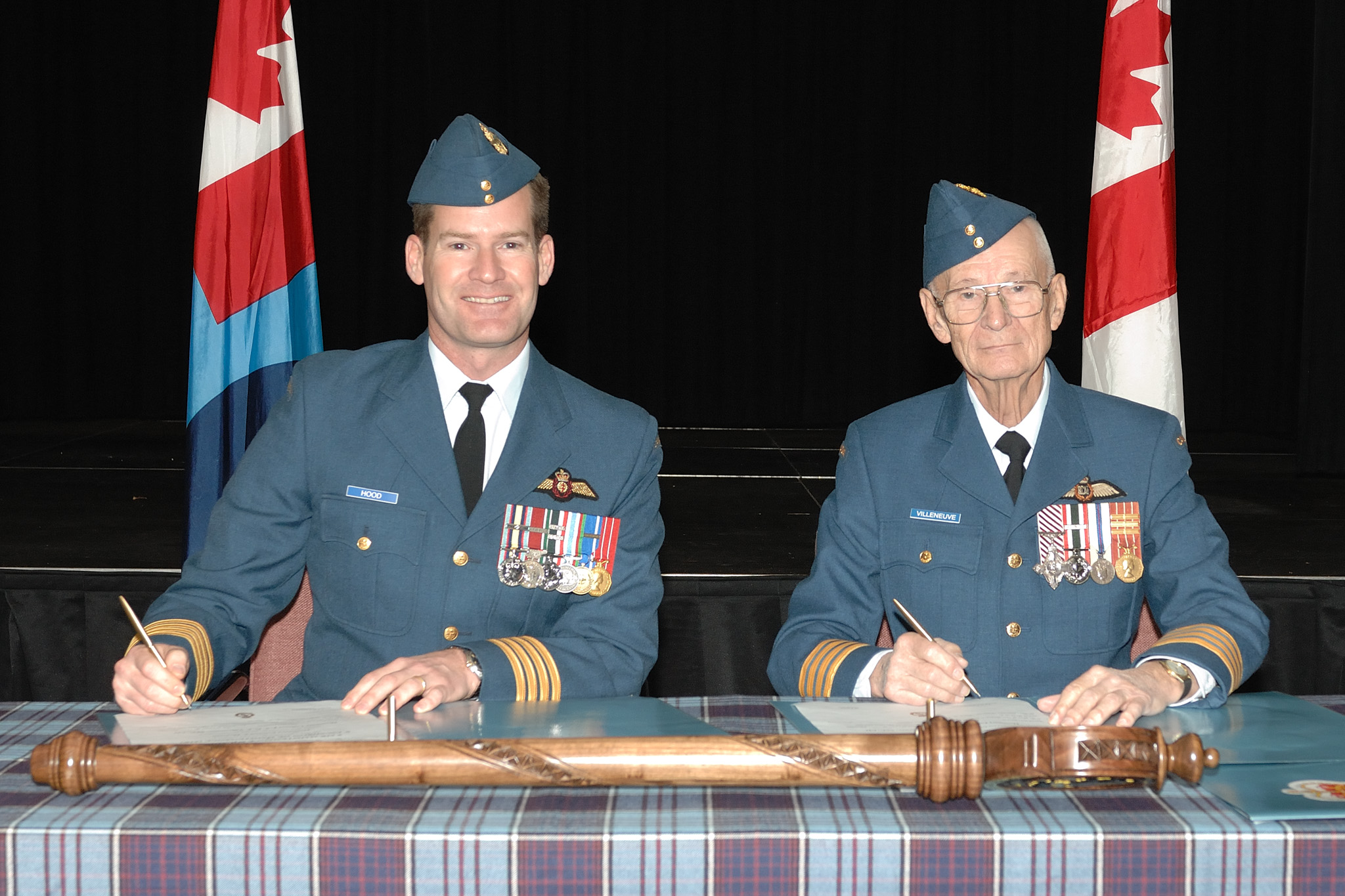 Colonel Mike Hood (left), commander of 8 Wing Trenton, Ontario, and Lieutenant-Colonel (retired) Fern Villeneuve sign the documents investing Lieutenant-Colonel Villeneuve as honorary colonel of 8 Air Maintenance Squadron in Trenton on December 4, 2008. PHOTO: Private Tina Gillies, TN2008-0816-01