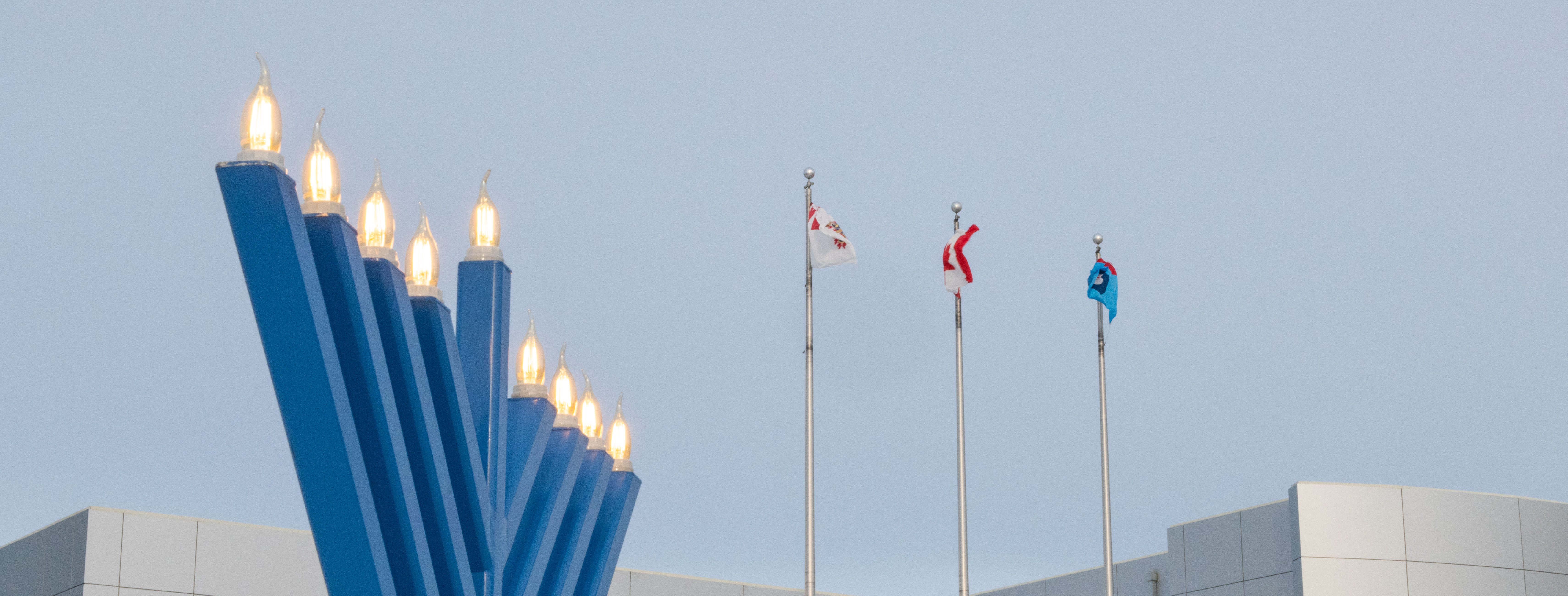 A large blue metal candlestick bearing nine illuminated candles – the centre candle taller than the others – stands in front of a concrete building with three flagpoles.