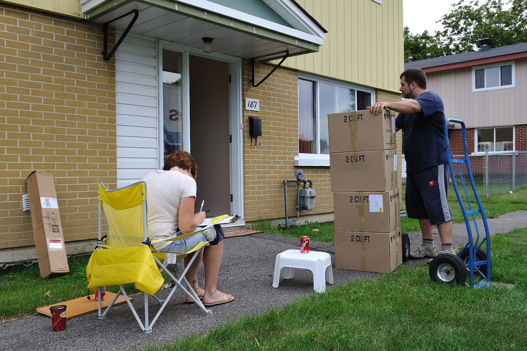 A woman writing on a clipboard sits in a lawn chair in front of a house with an open door, while a man standing by a dolly has his hands on the top box in a stack of four, and looks through the open door.