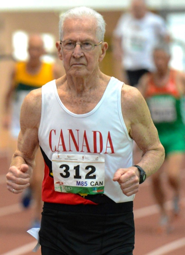 A senior man wearing Canada bib 312 runs on a track.