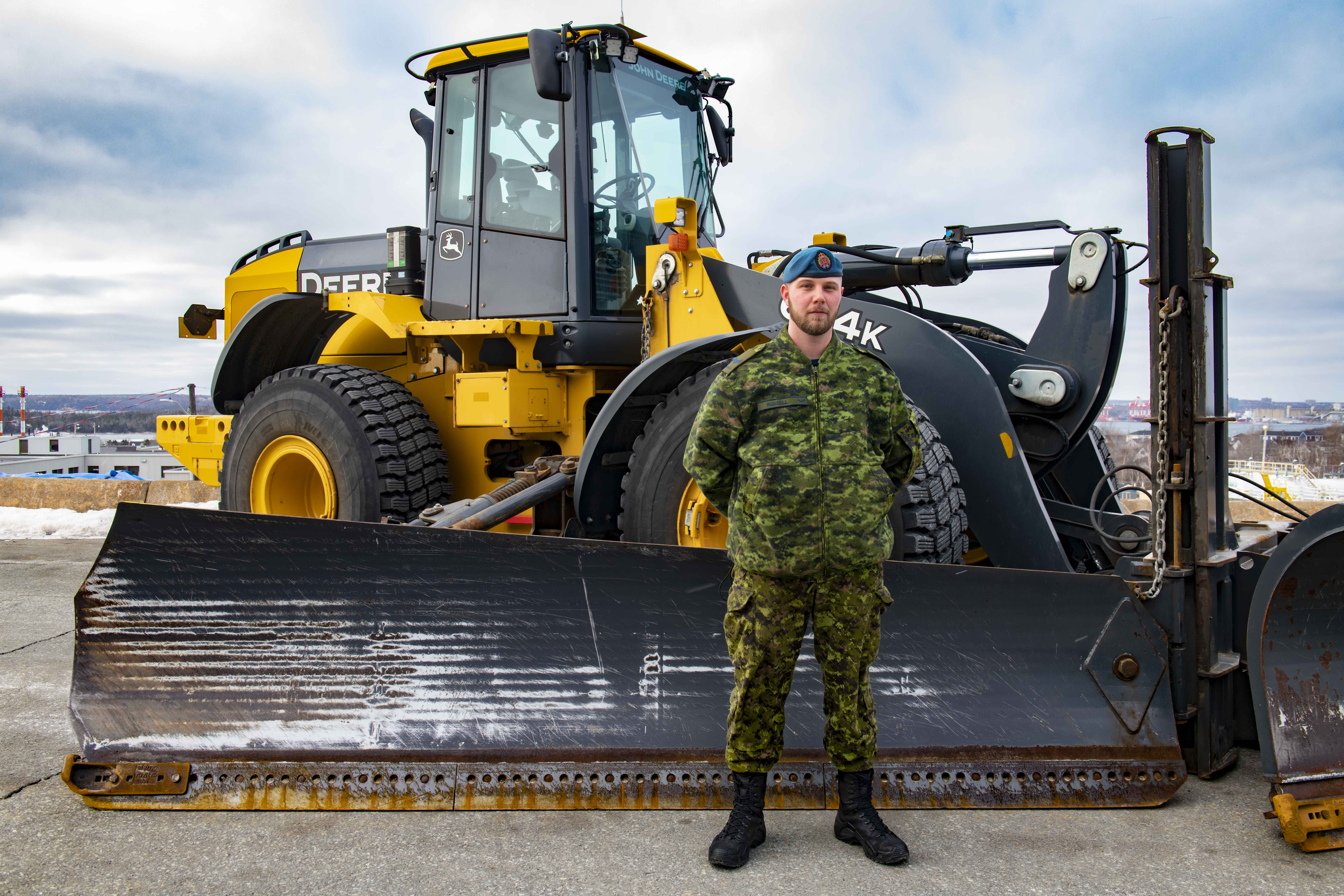 A man wearing a disruptive pattern uniform stands in front of a large heavy-equipment vehicle with a blade on the front.