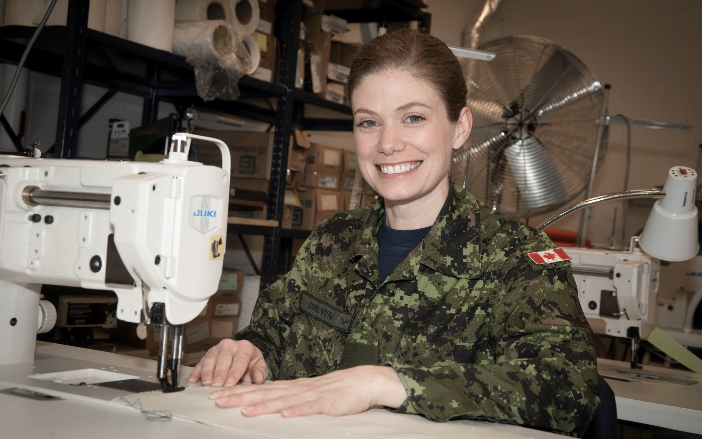 A smiling woman wearing a disruptive pattern uniform sitting at a table works with a sewing machine.