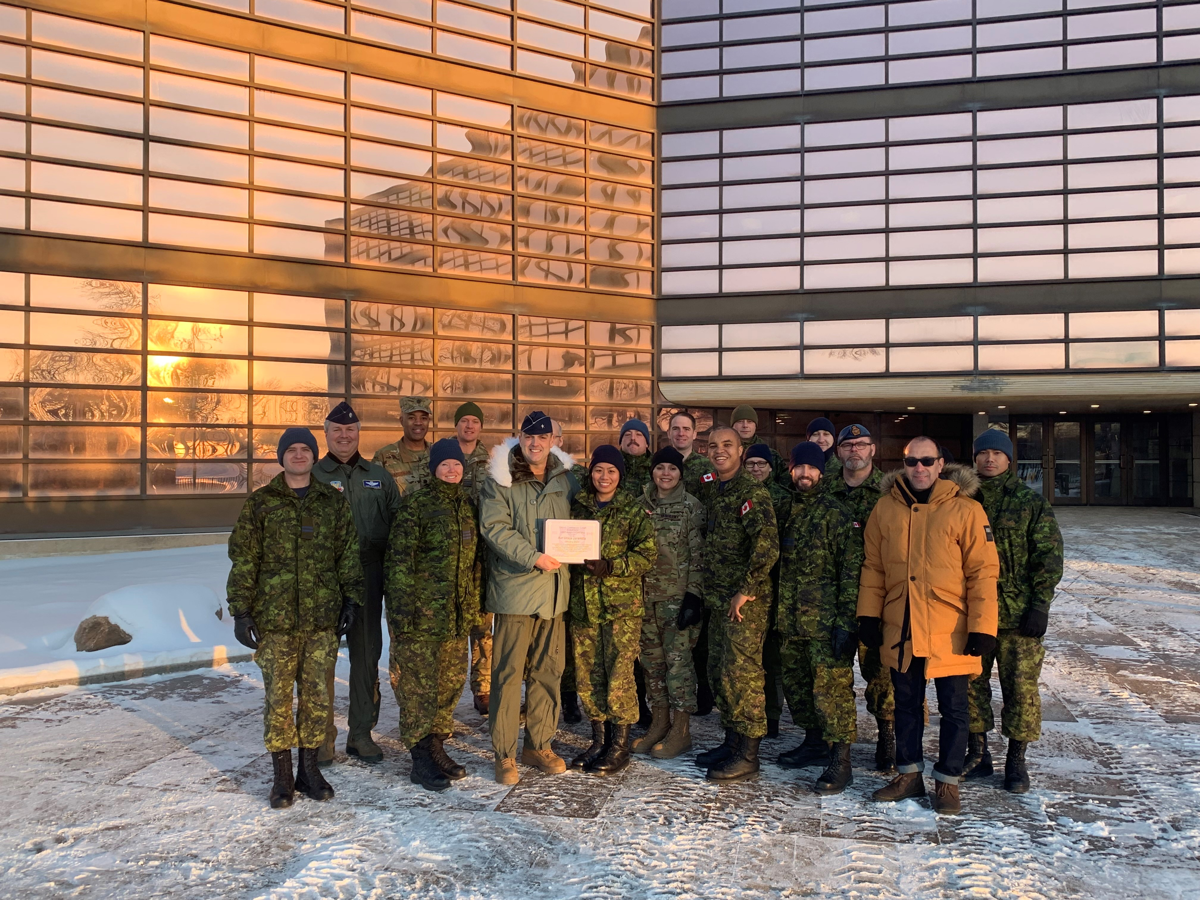 A large group of people stand in the snow near a large glassed building; a uniformed man gives a certificate to a woman wearing a disruptive patterned uniform.