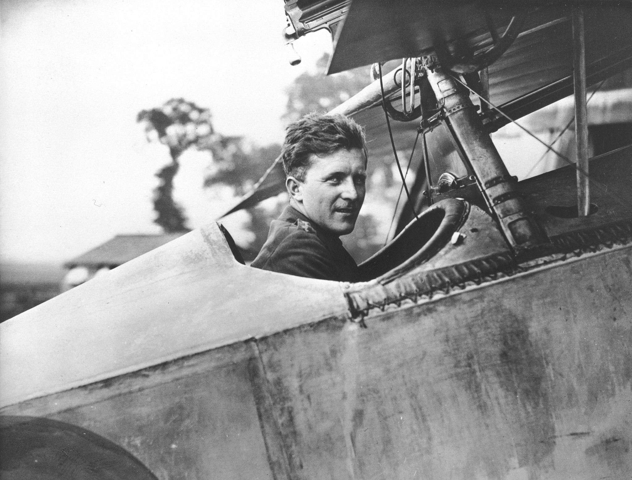 A black and white photo of man sitting in the cockpit of First World War fighter biplane.