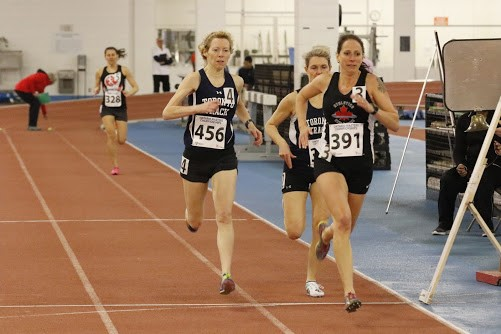 Four women run on a track during a track and field competition.
