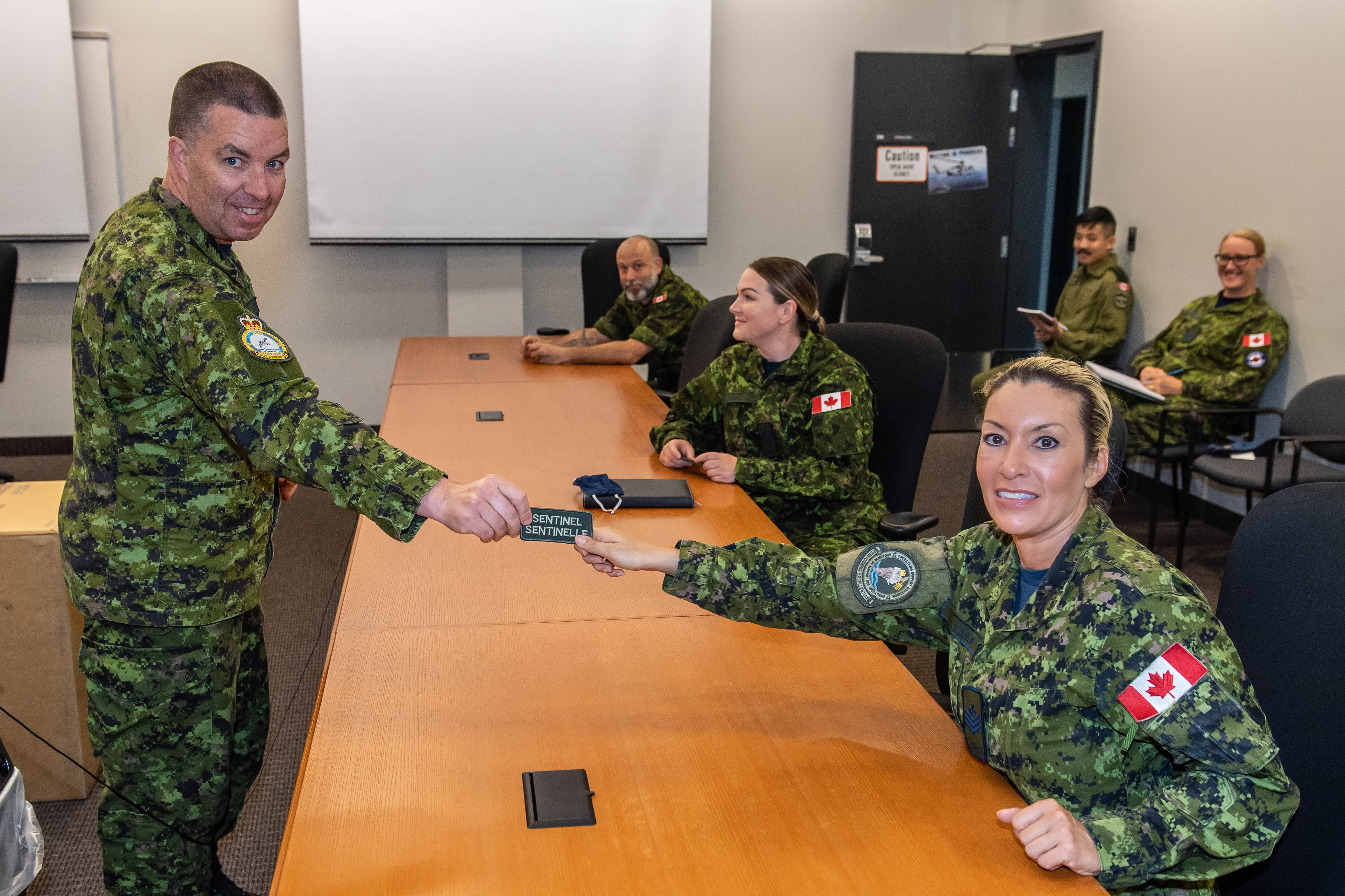Six people wearing military uniforms are in a room. Five of them sit on chairs and the one who is standing gives a patch badge to one of the people sitting.