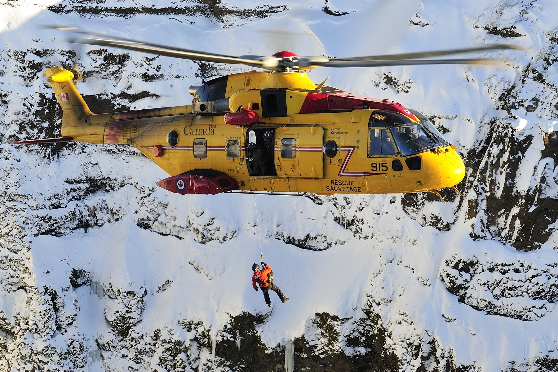 Sergeant Kevin O'Donnell, a search and rescue technician from 103 Search and Rescue Squadron, based in Gander, Newfoundland and Labrador, is hoisted down from a CH-149 Cormorant helicopter to participate in a mountain rescue scenario during a search and rescue exercise held in Iceland on February 10, 2016. PHOTO: Master Corporal Johanie Maheu
